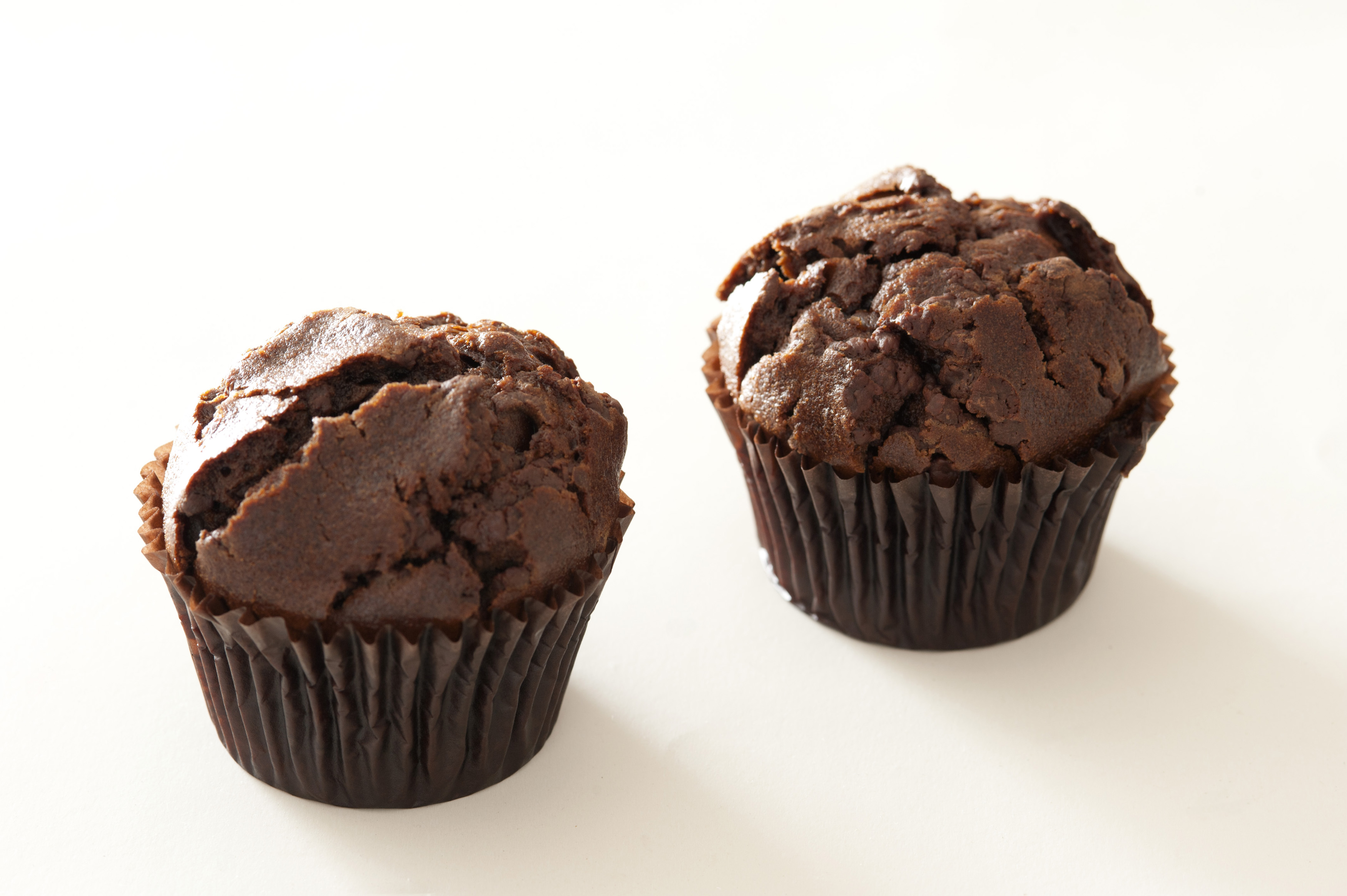 Pair of yummy baked chocolate muffins with cracked tops and subtle shadows over white background
