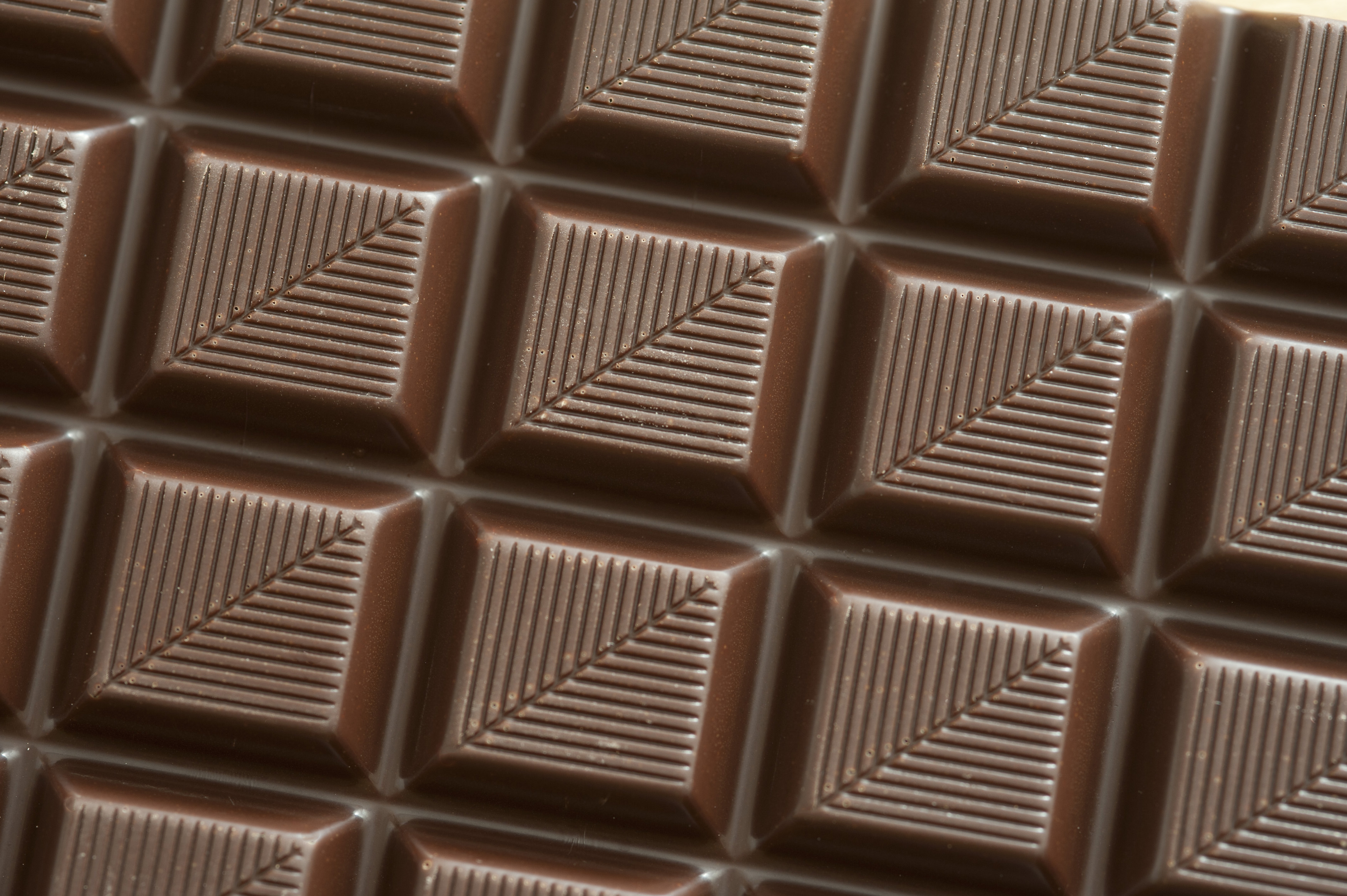 Bar of dark chocolate with decorative pattern of diagonal lines in a close up full frame texture and pattern