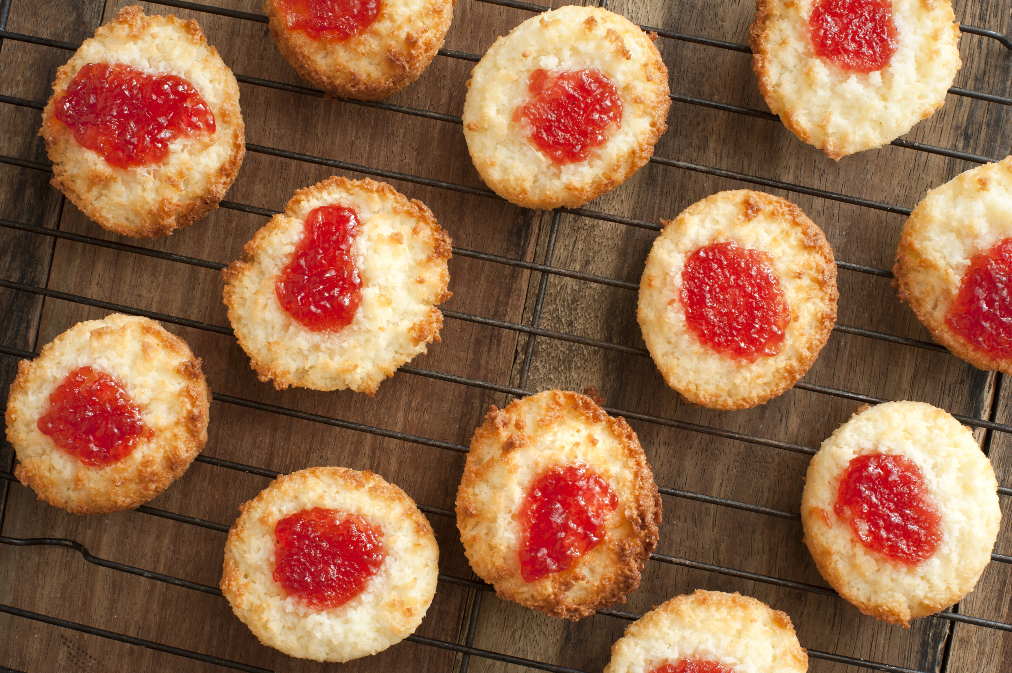 Tasty home baked coconut drop cookies topped with colorful red strawberry jam cooling on a wire rack in a kitchen, overhead view