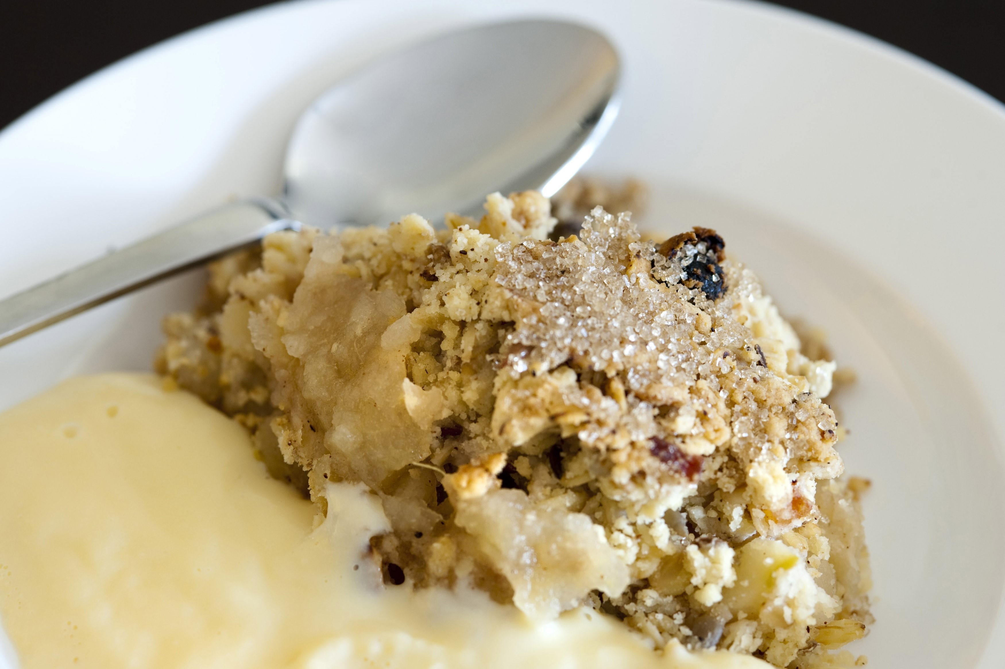 Serving of spicy apple crumble topped with raisins, sugar and cinnamon and served with custard