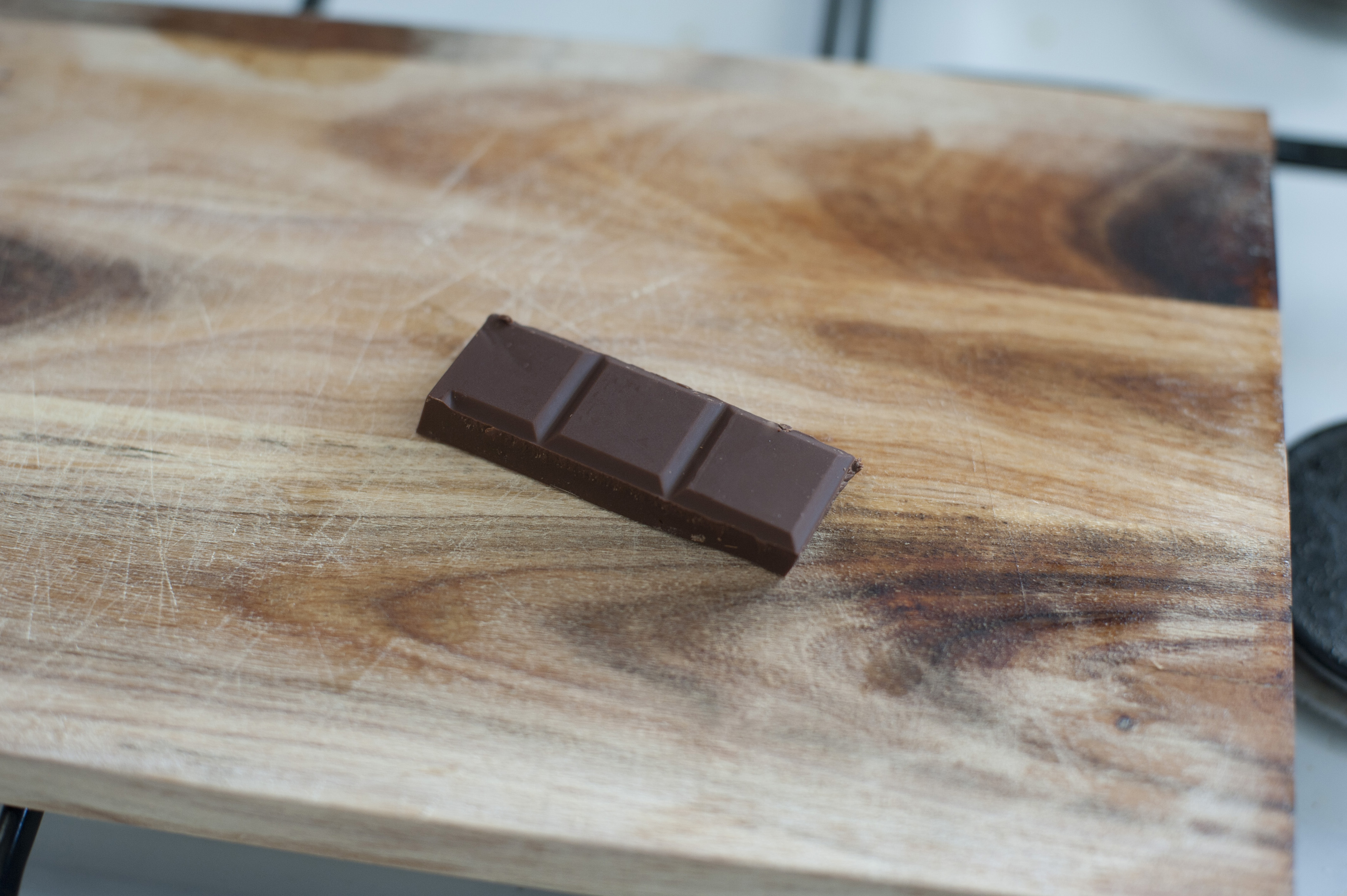 First person perspective view on dark baking chocolate squares bar in three sections over cutting board