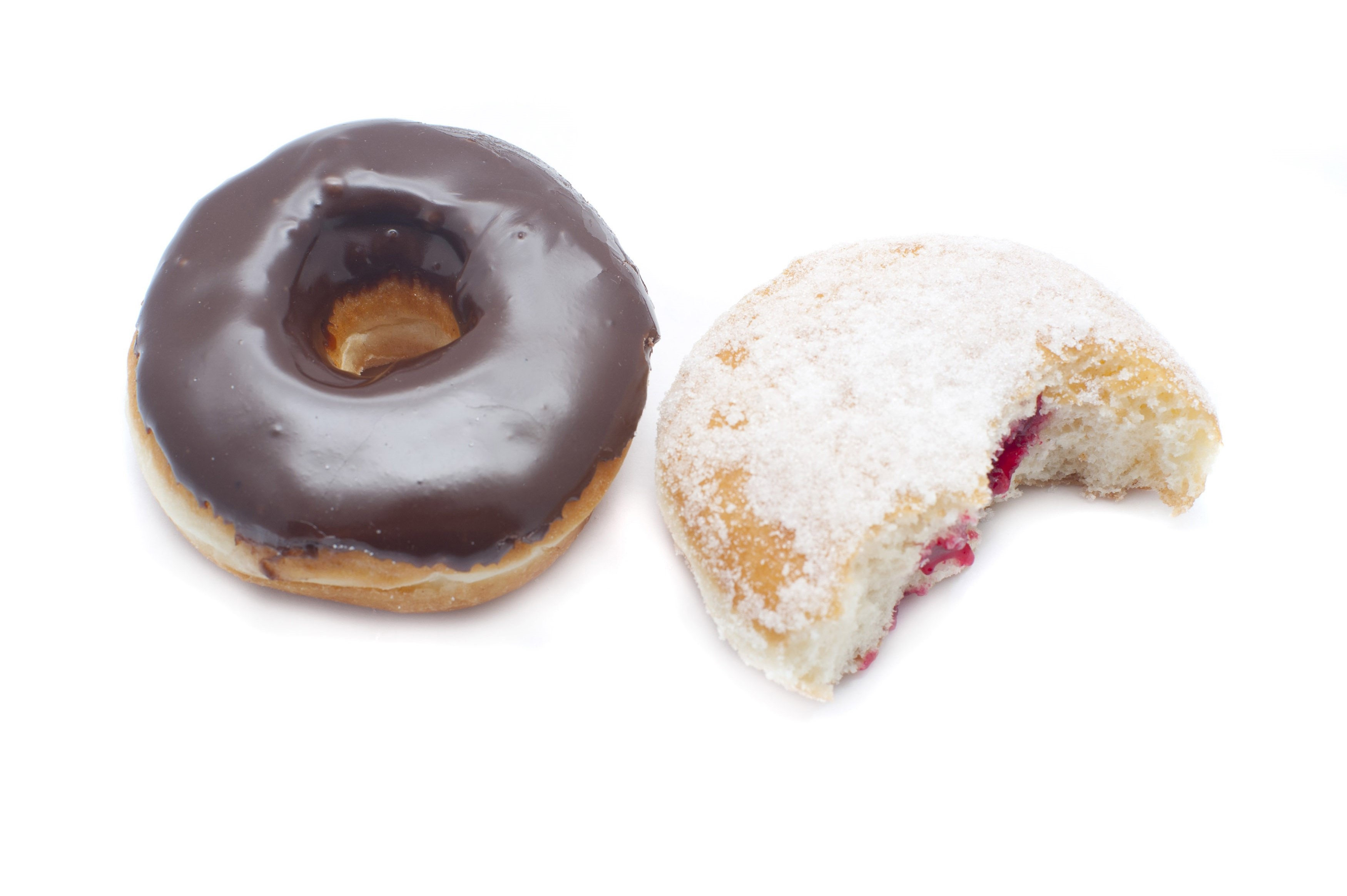 High angle view of a fresh chocolate ring donut and sugared jam doughnut broken open to expose the filling