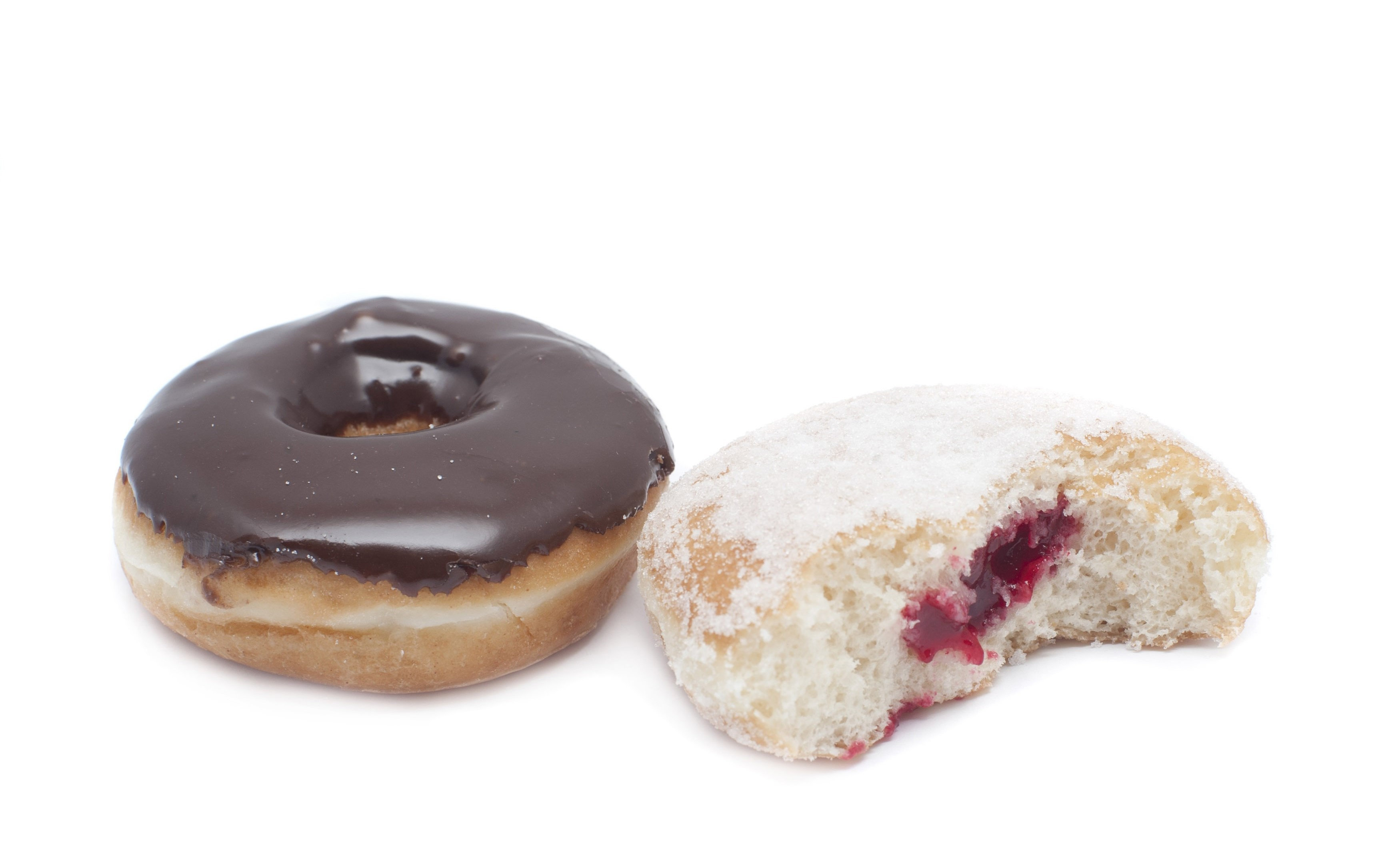 Two fresh ring doughnuts, one covered in chocolate frosting and one with a jam centre opened to display the filling on white