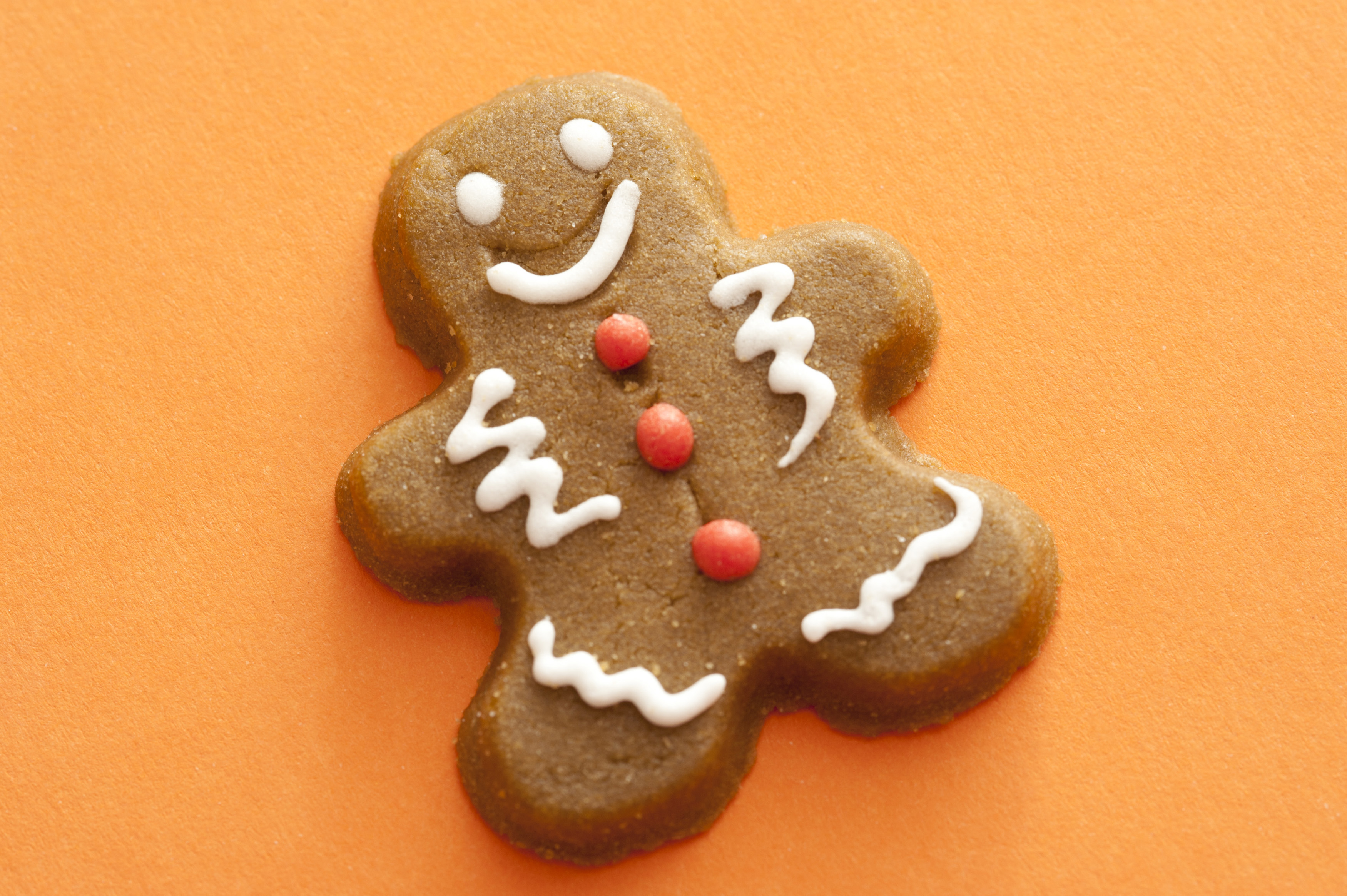 Festive decorated gingerbread man with icing accents on a colorful orange background, close up view with copy space