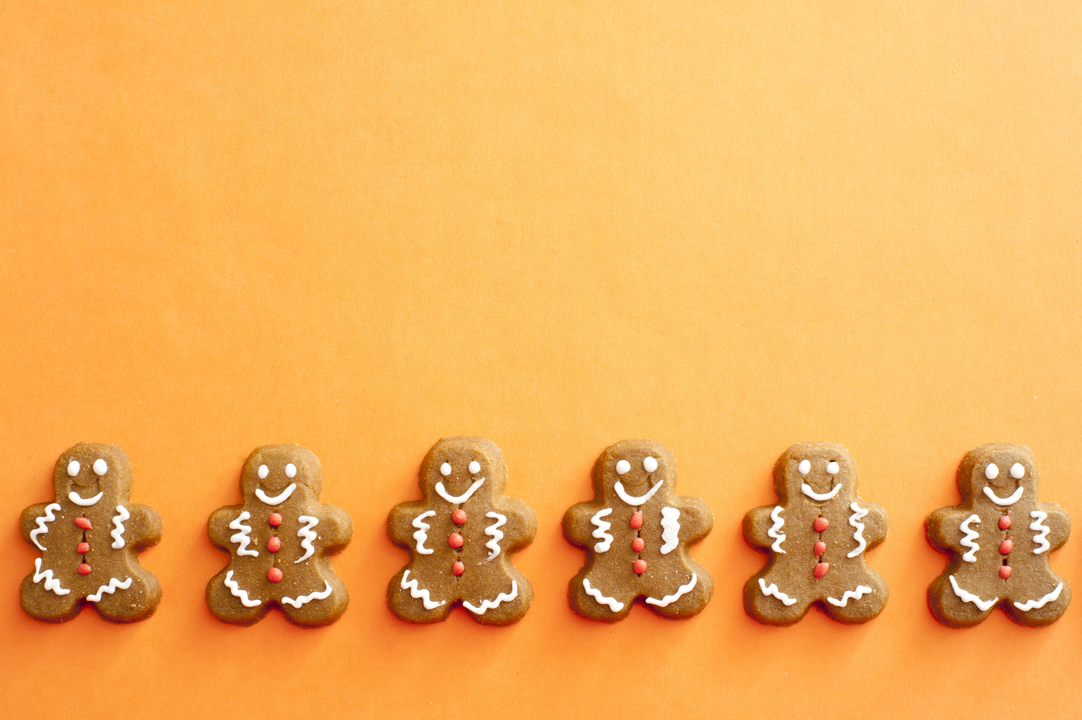 Row of six gingerbread men decorated with white and orange icing details under section of copy space