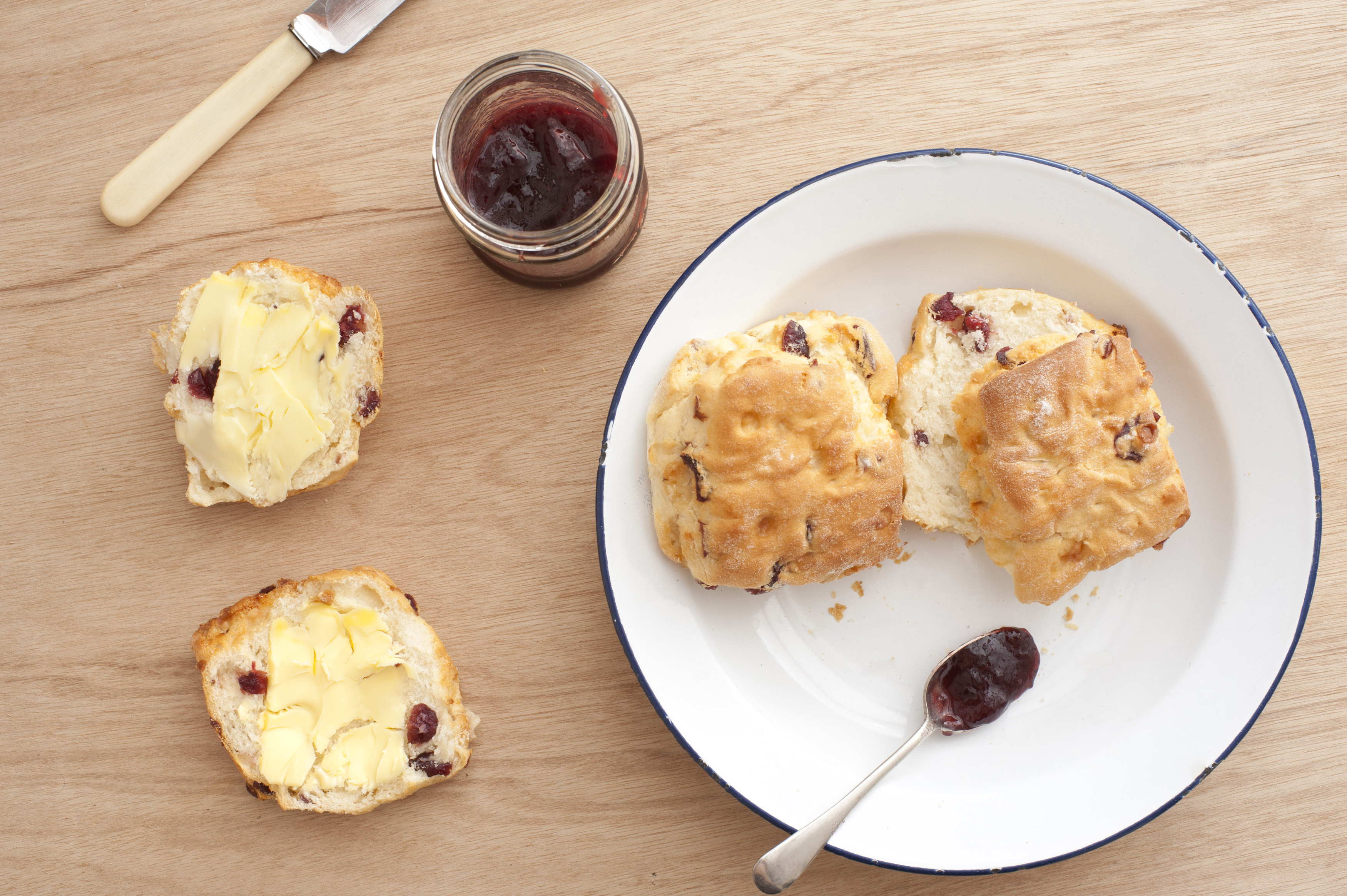 Freshly baked buttered scone or rock cake with raisins and fruit pieces with a jar of strawberry jelly and further cookies on a white plate alongside, overhead view