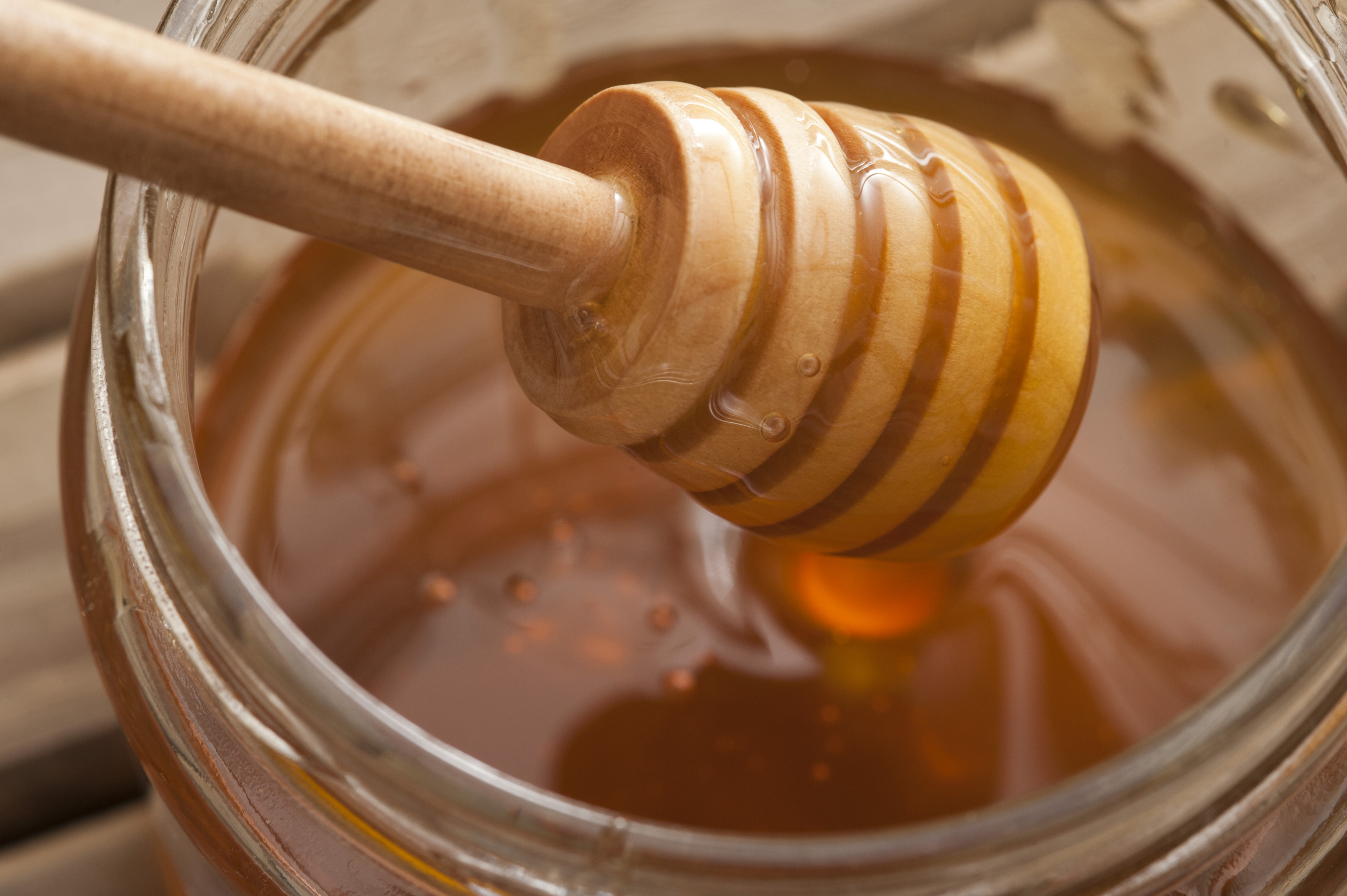 Close up of ribbed wooden dipper in large glass jar filled up with sweet yellow honey