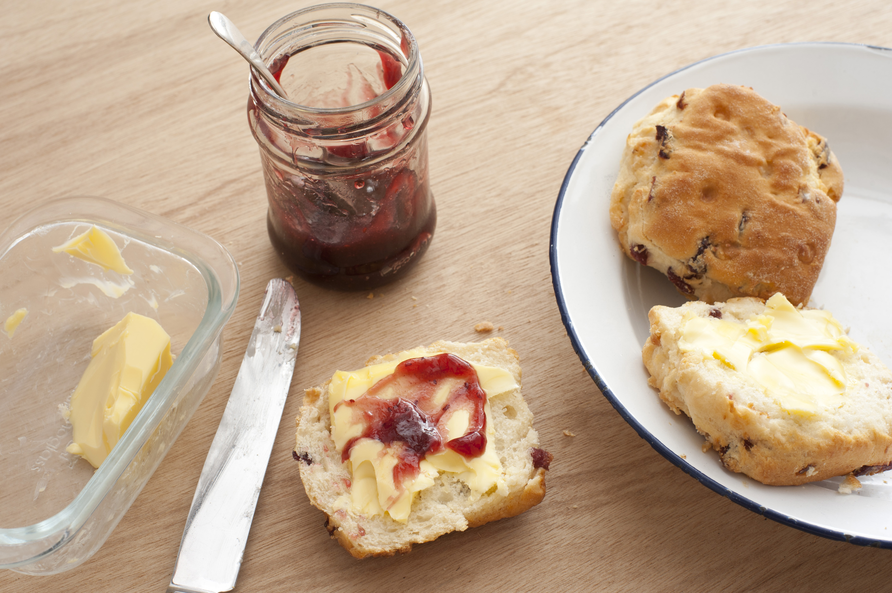 Fresh buttered homemade fruity raisin scones with strawberry jam served on a plate on a wooden table for a tasty snack
