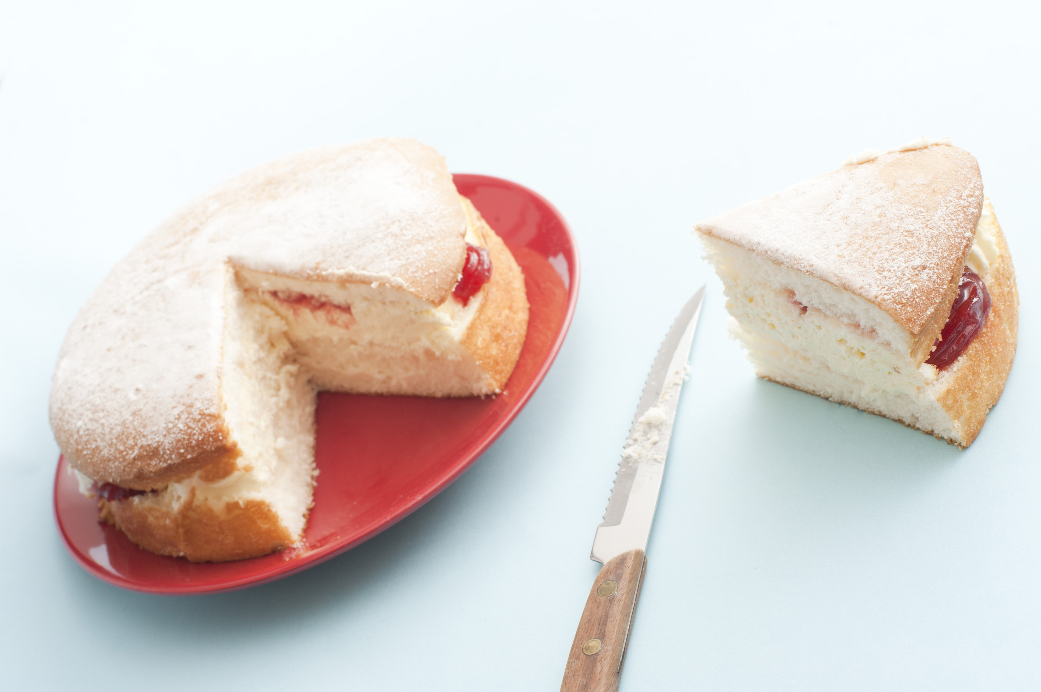 Freshly baked jam sponge cream cake with a generous slice on the side alongside a knife, served on a red plate