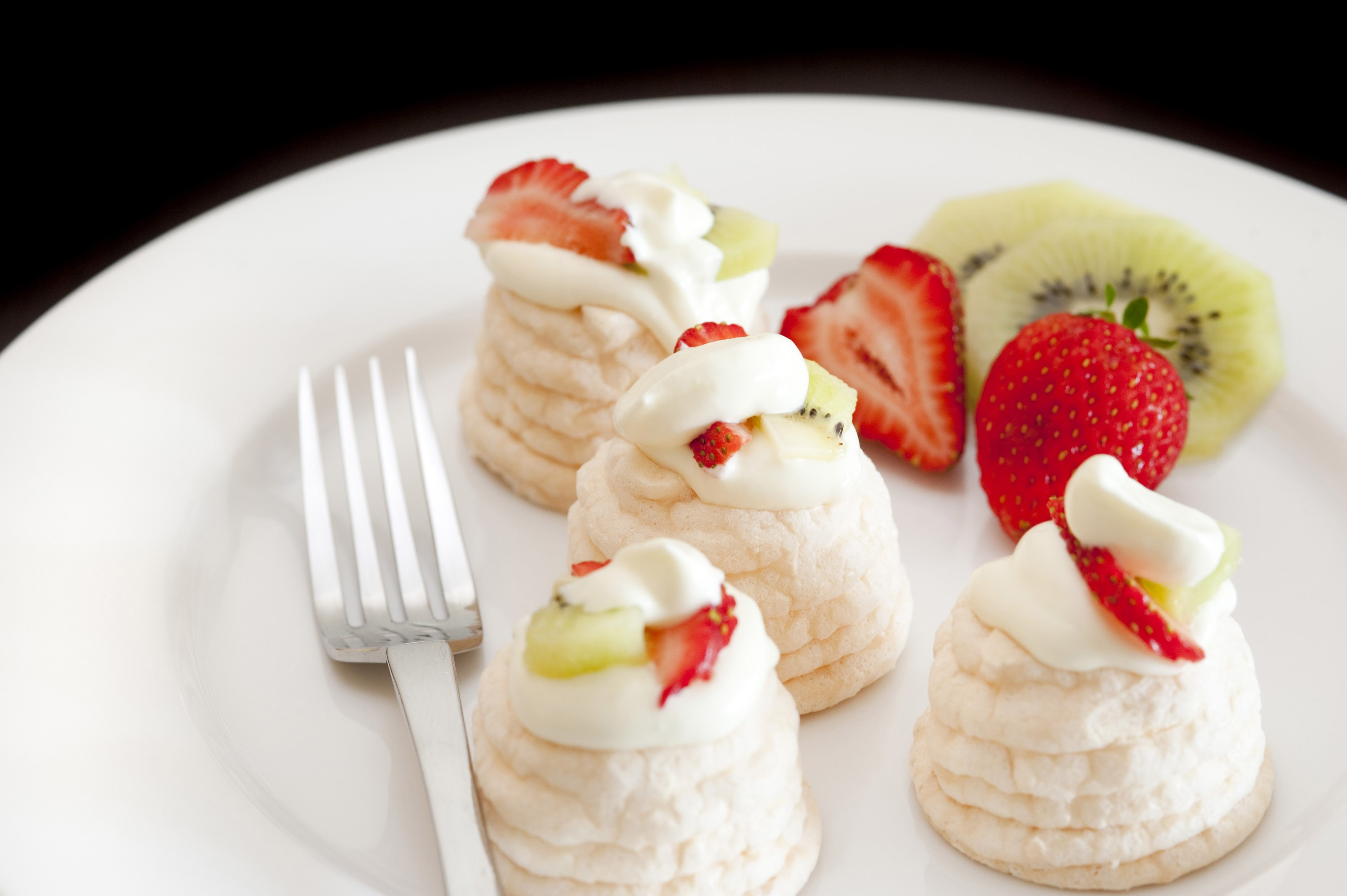 Serving of crisp meringue cones filled with whipped cream and fresh fruit for a healthy dessert