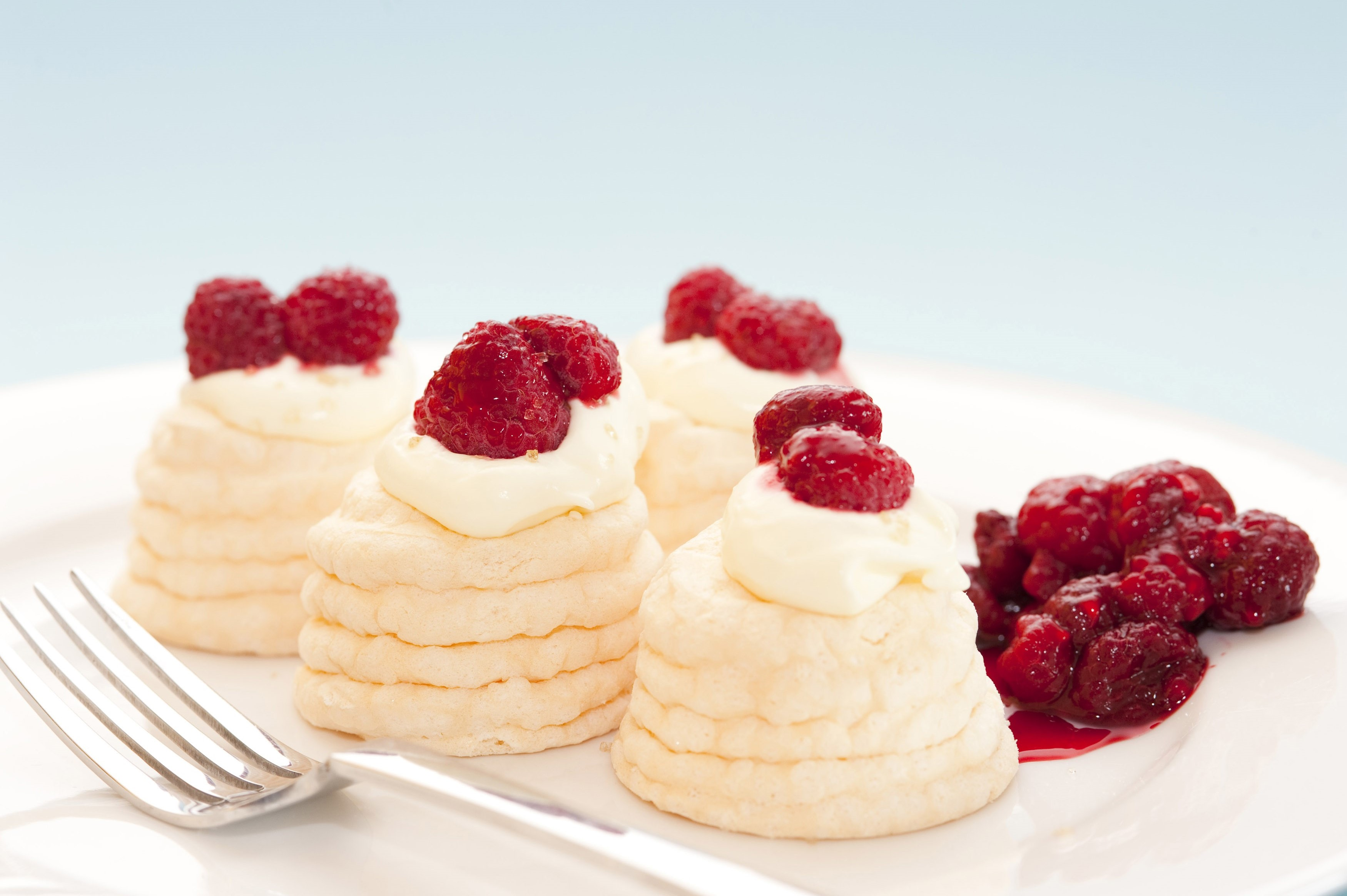 Decorative twirled meringues filled with whipped cream and topped with fresh raspberries served on a plate with a fork