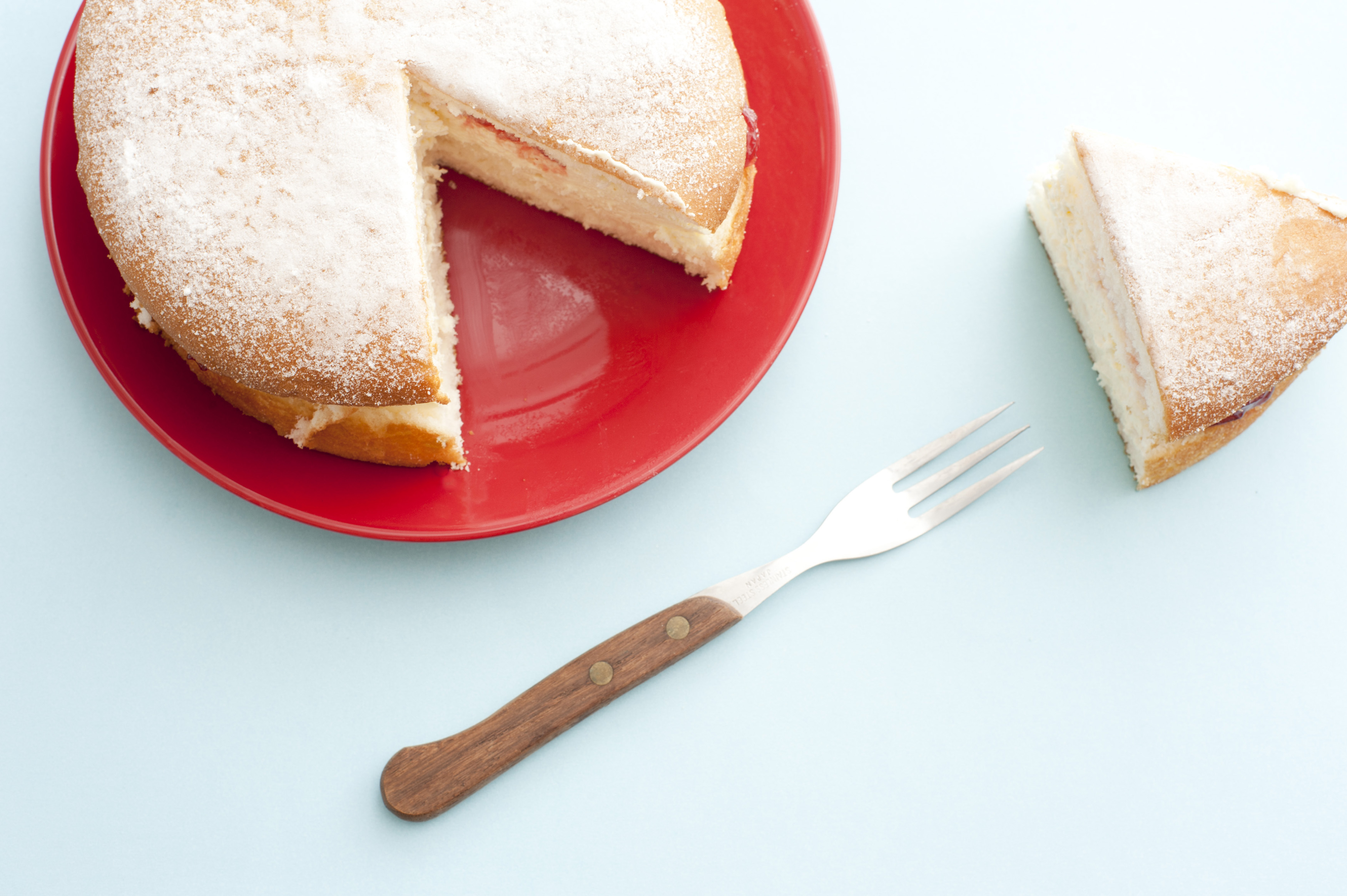 Top down view of cut sugar coated sponge cake on red round plate beside fork and cut piece on table