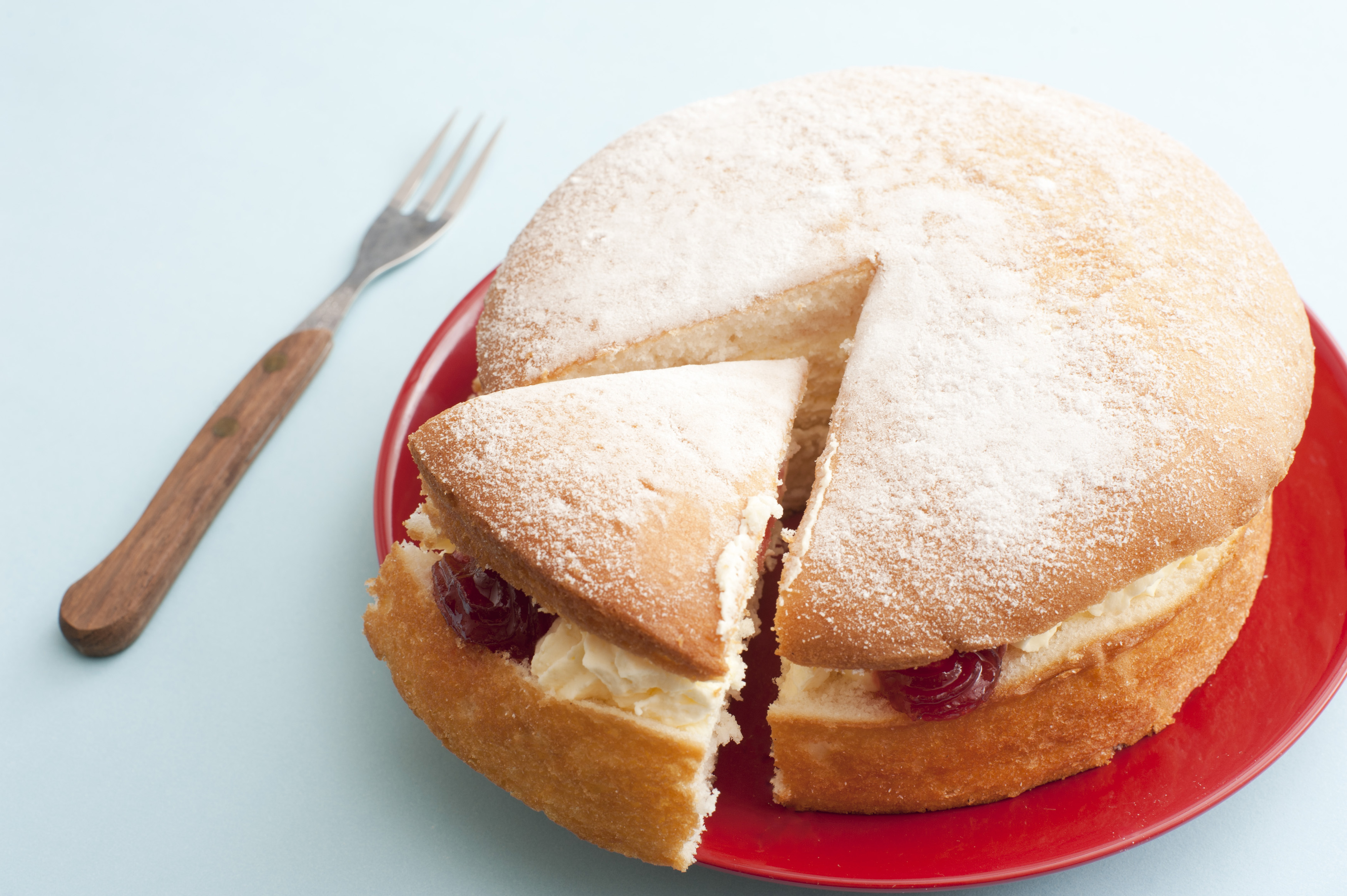 Freshly baked plain vanilla sponge cake filled with cream and strawberry jam with a single slice cut and moved to the side of the red plate , close up high angle view