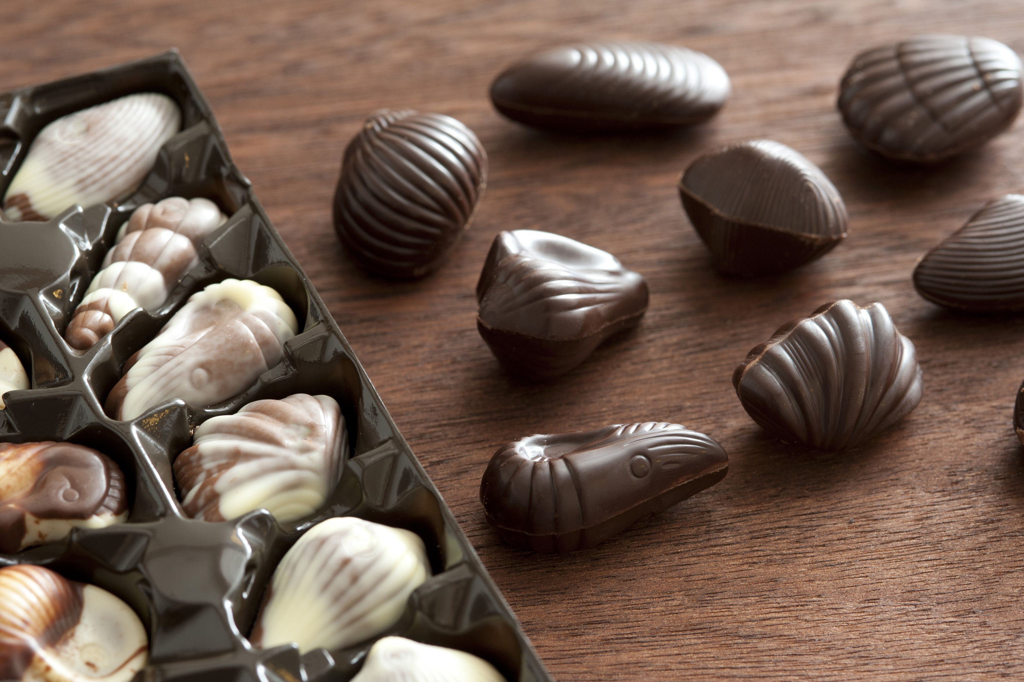 Assorted speciality shell shaped chocolates in dark chocolate, milk chocolate and white chocolate, some in the original packaging and others alongside on a wooden table