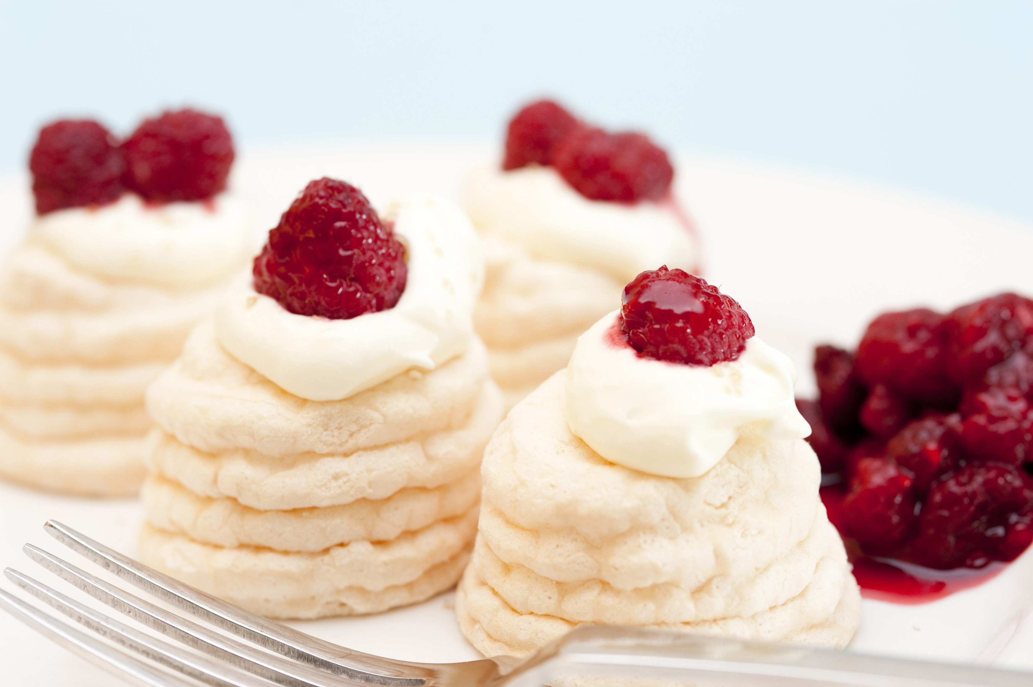 Individual twirled meringue cases filled with whipped cream and topped with fresh raspberry compote served on a plate