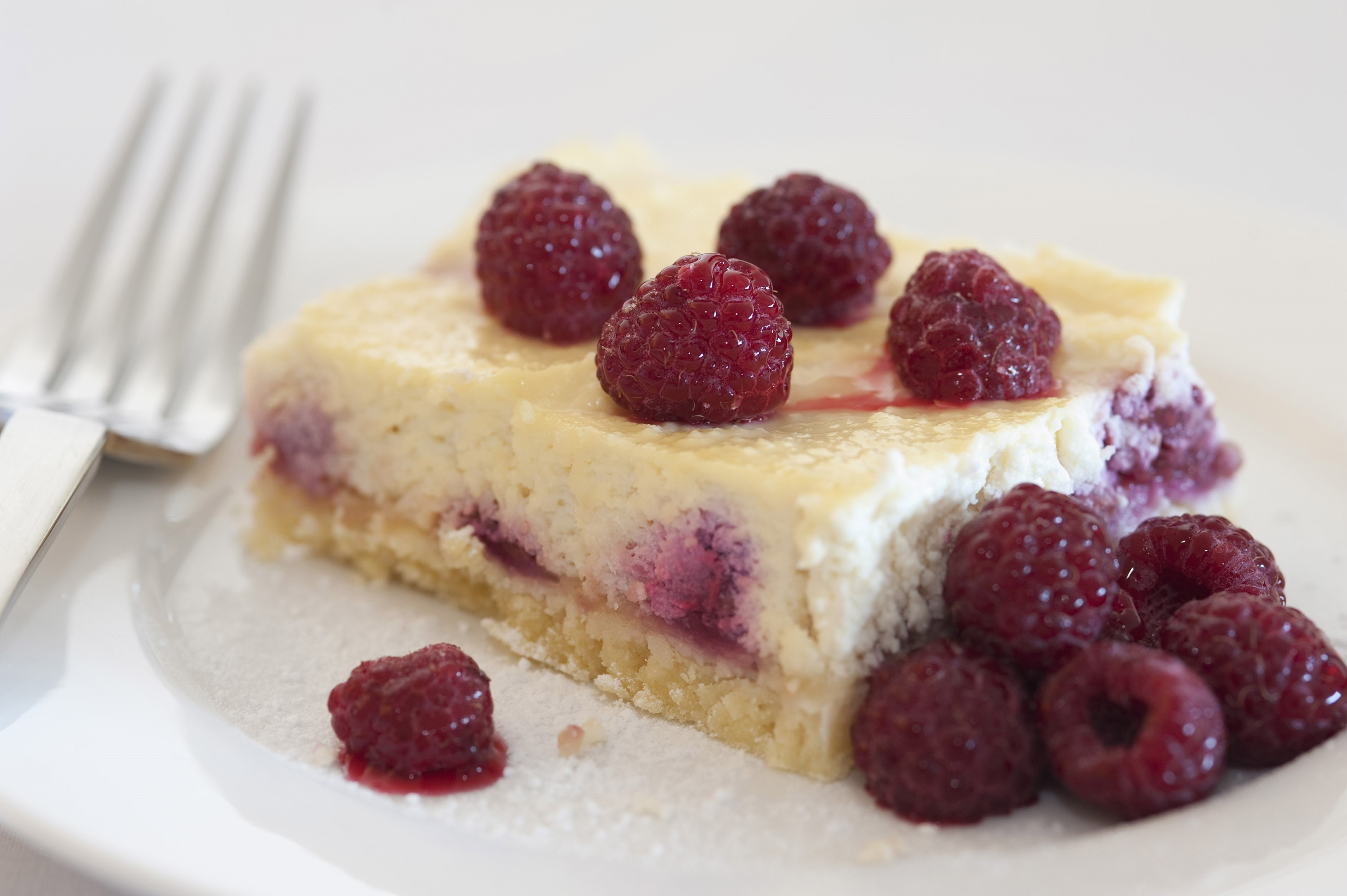 Slice of freshly baked raspberry ricotta cheesecake with fresh whole ripe raspberries served on a side plate