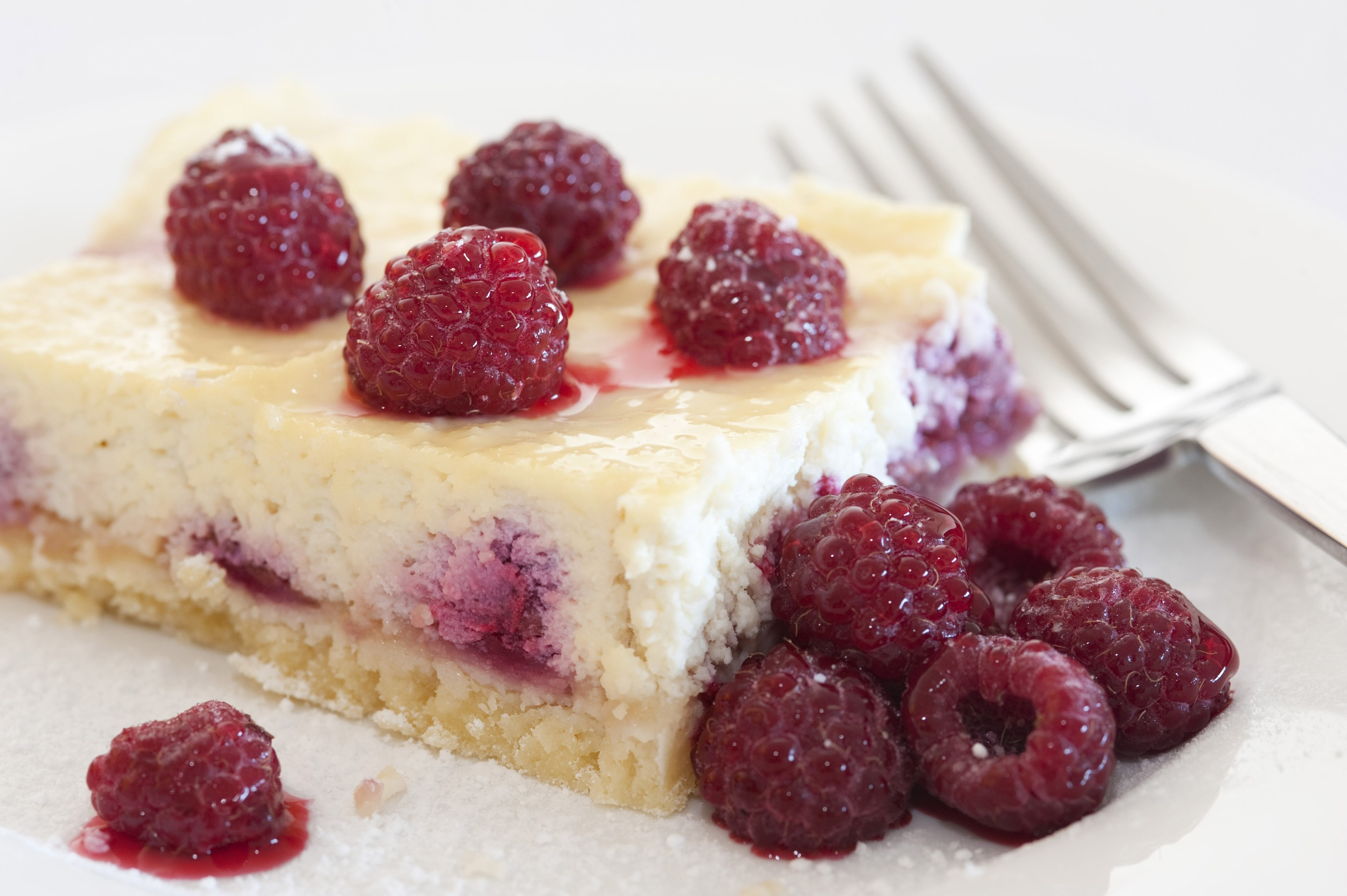 Raspberries on a slice of freshly baked ricotta cheesecake, close up view with a fork