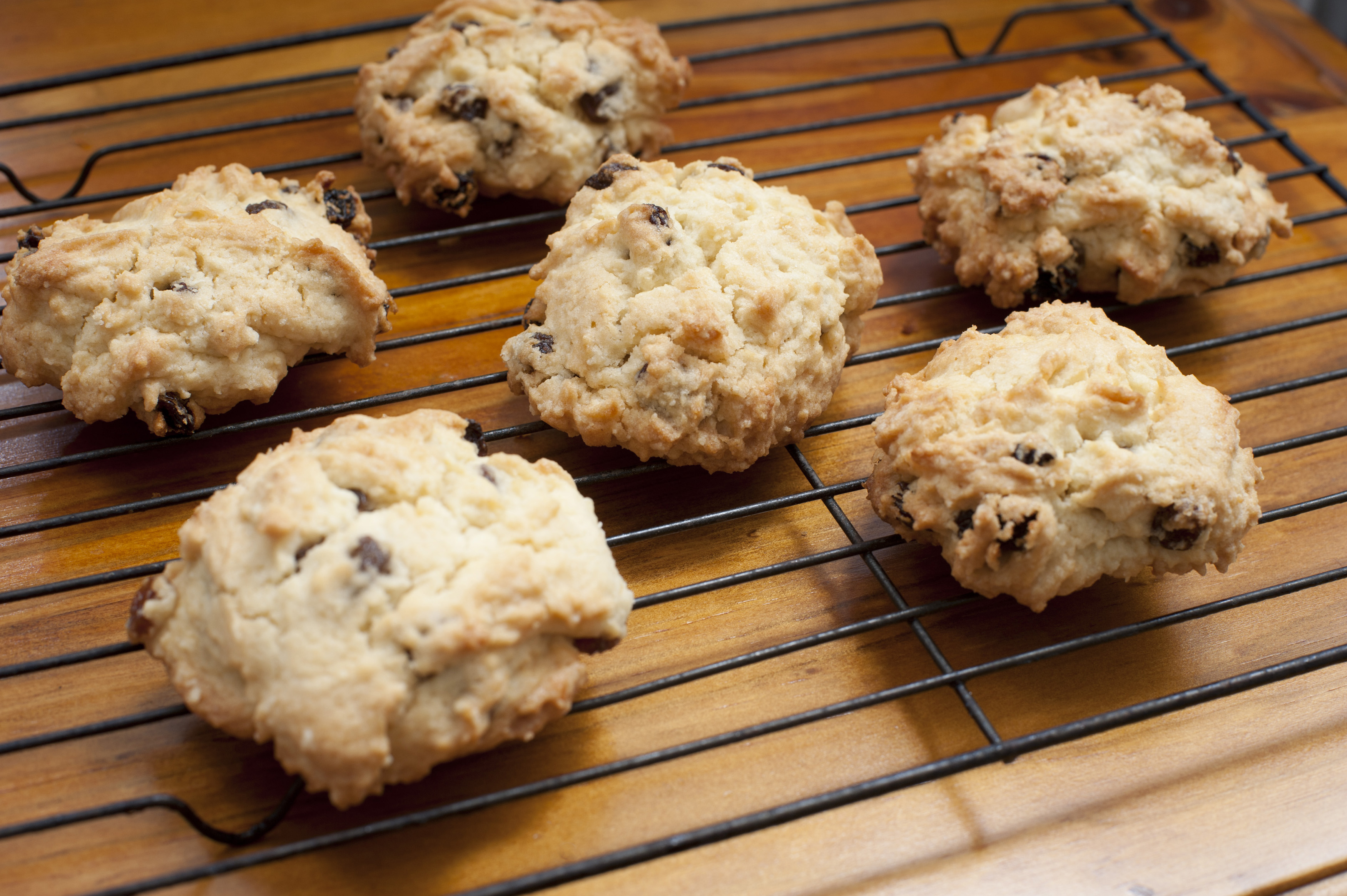 Five delicious rock cake type cookies with dates, raisins or chocolate pieces on oven rack over wooden table