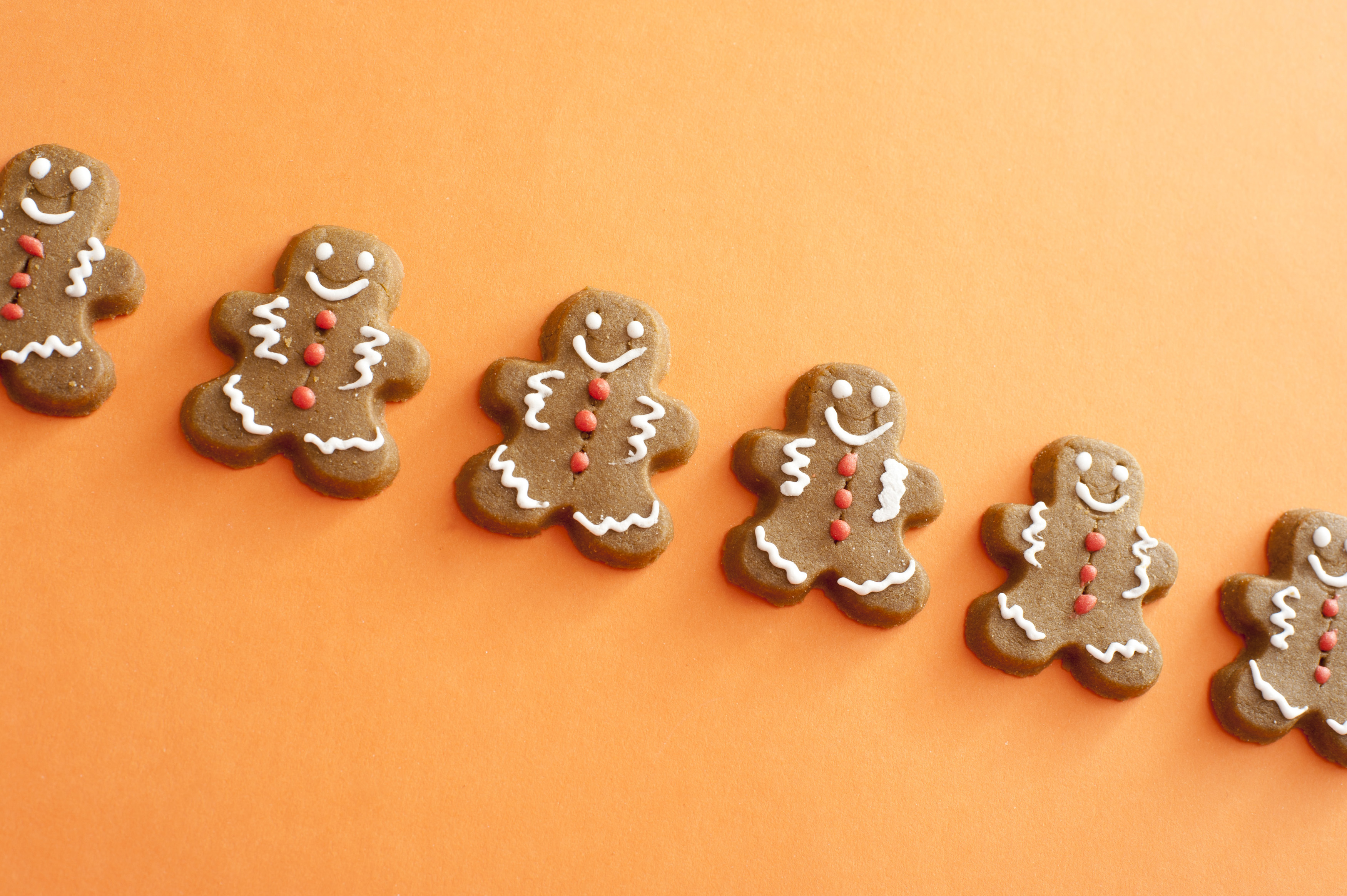 Single line of smiling gingerbread men cookies with white and red candy decorations detailing the face, arms and legs