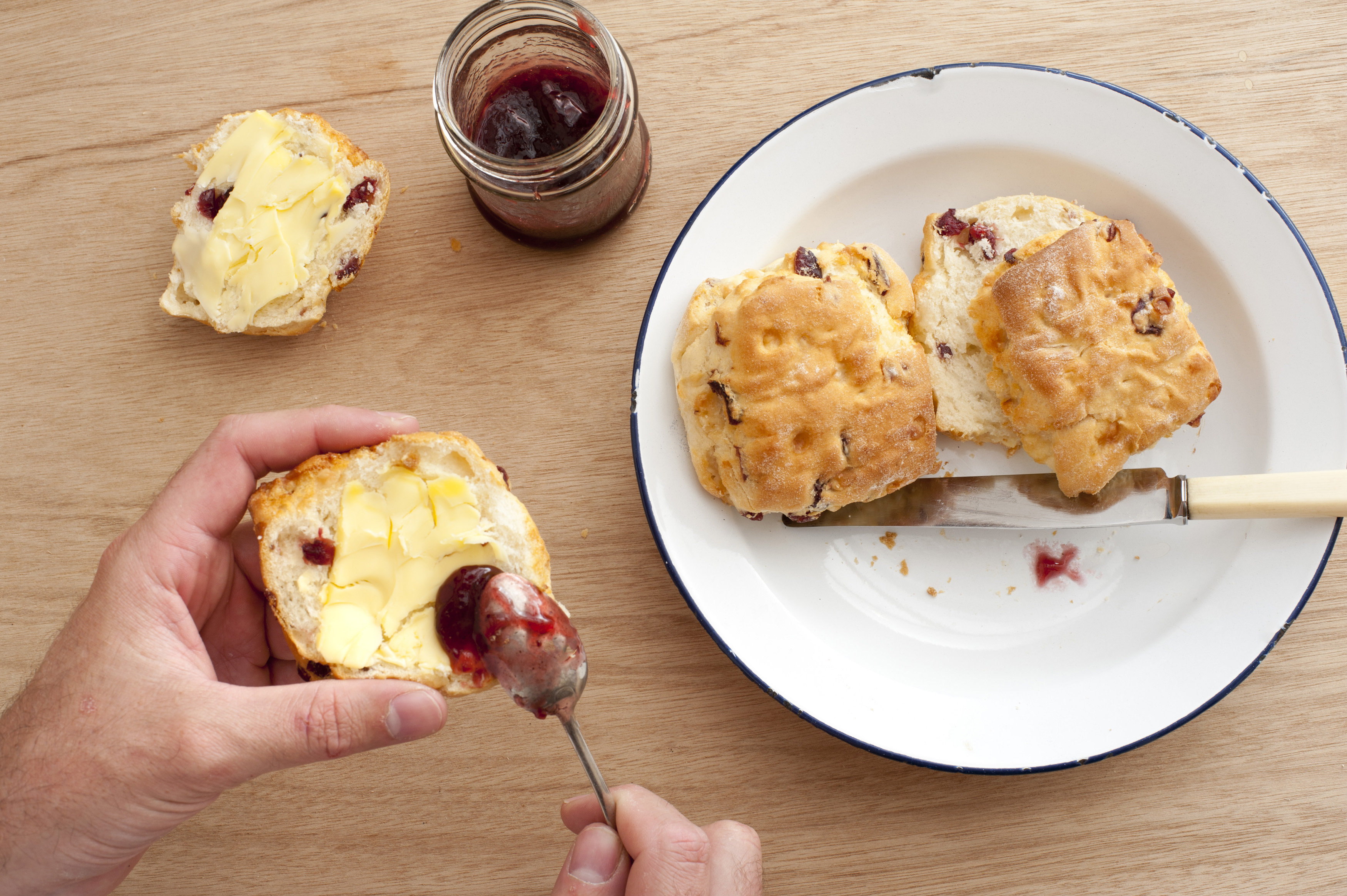 Top down view of hands applying strawberry jam on muffins using spoon with butter next to plate and knife