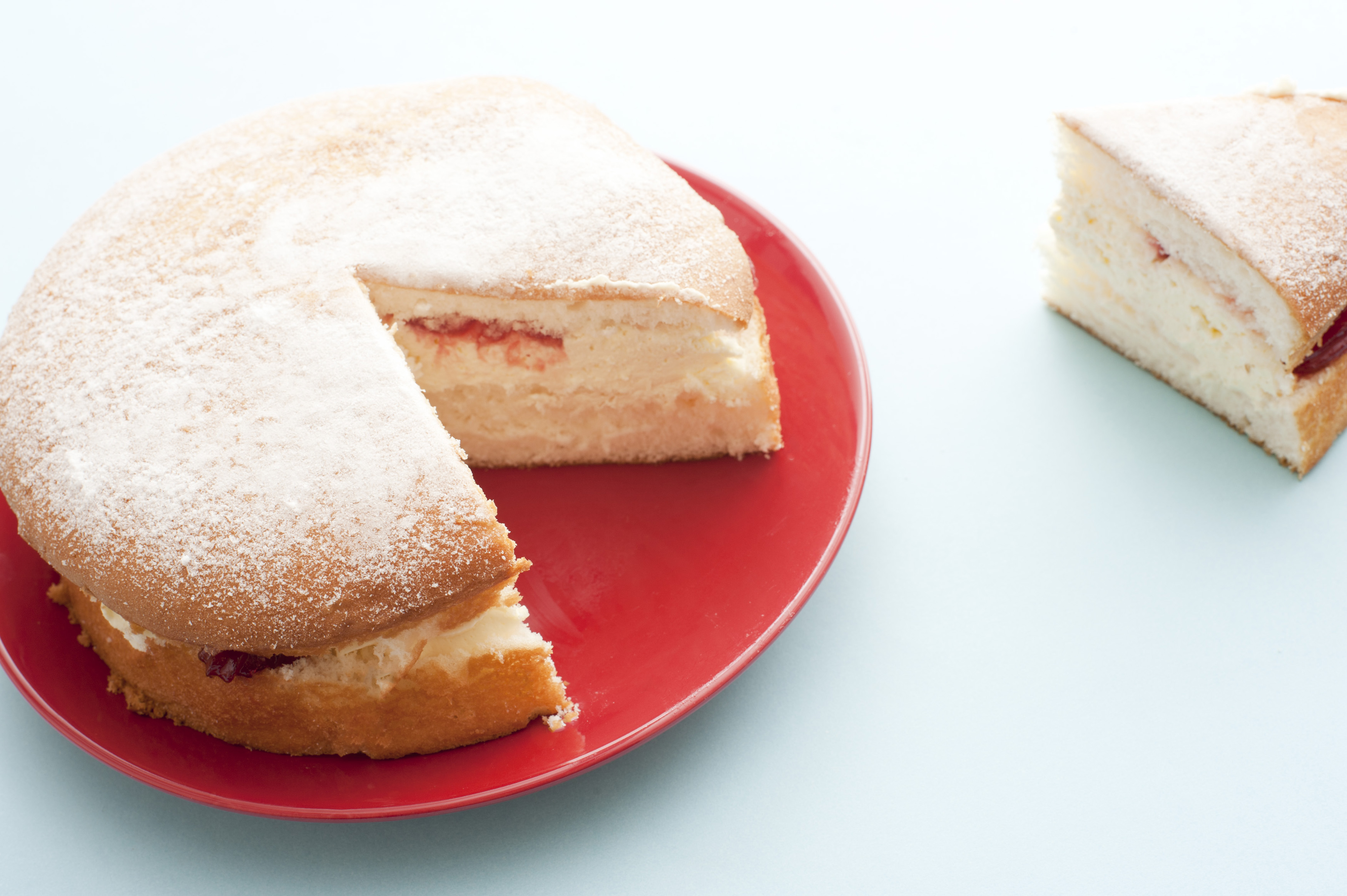 Freshly baked simple sponge cake sprinkled with icing sugar and filled with cream and strawberry jam with one slice cut and moved to the side of the plate