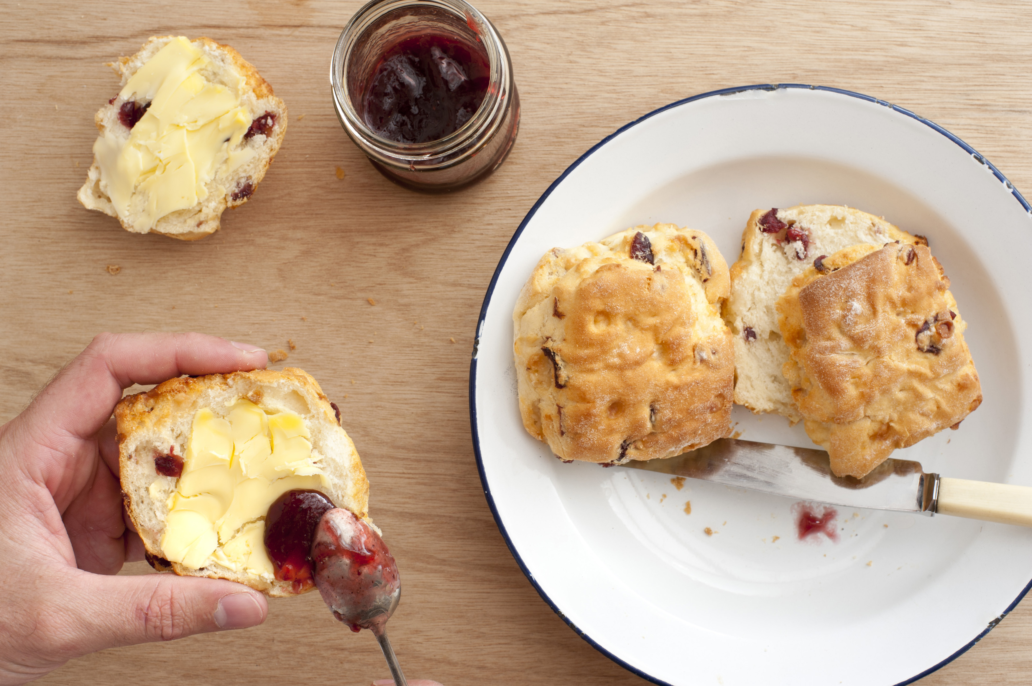 First person perspective of hands spreading strawberry jam on buttered crispy scone biscuits with spoon over plate on light brown wooden table