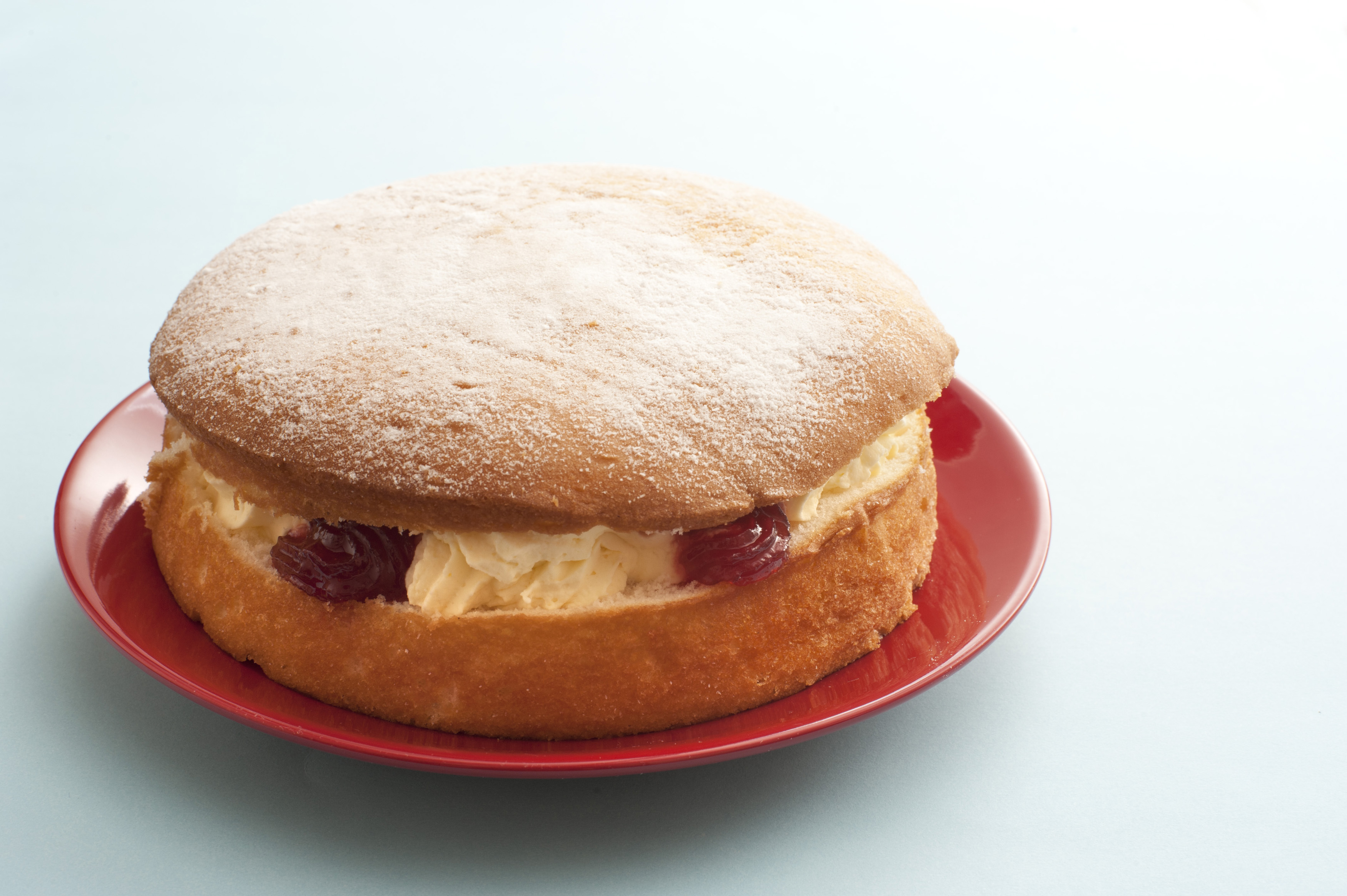 Delicious single little round victoria sandwich sponge cake filled with cream and fruit on red plate over white table