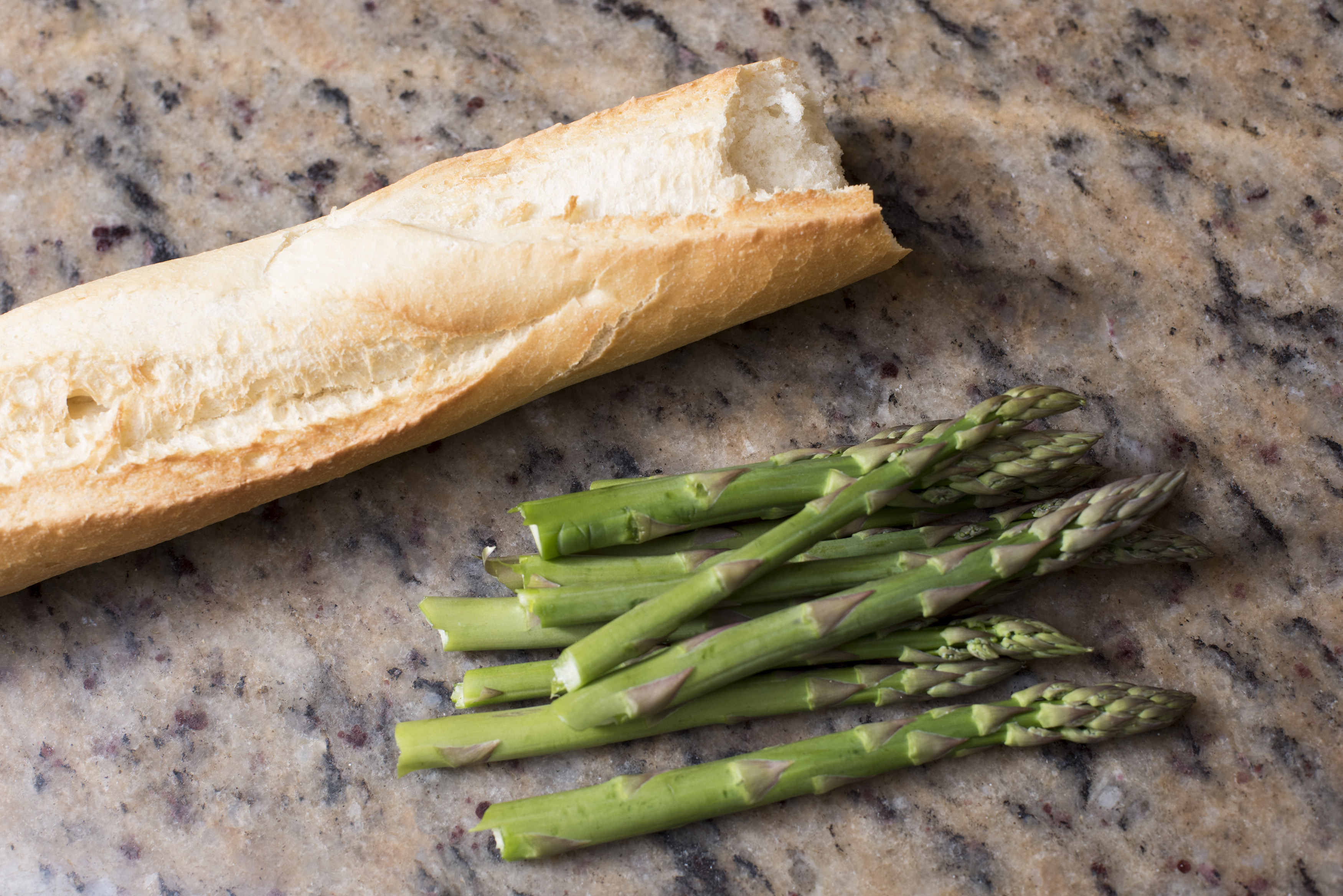 Fresh green asparagus tips and a crusty white baguette on a marble counter top in the kitchen