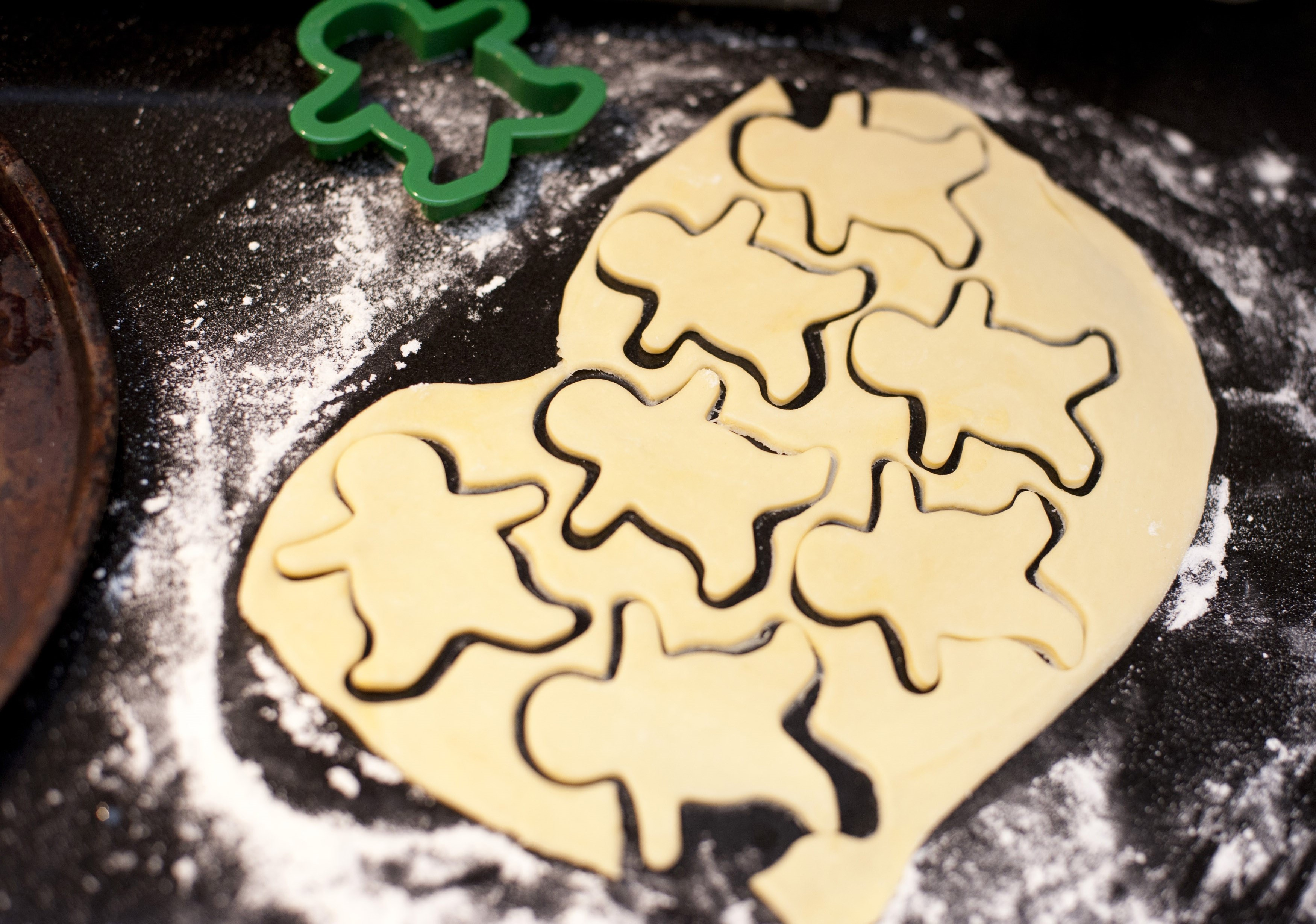 Overhead view of a cookie cutter and thinly rolled pastry dough with cut out cookie shapes for making biscuits while baking in the kitchen