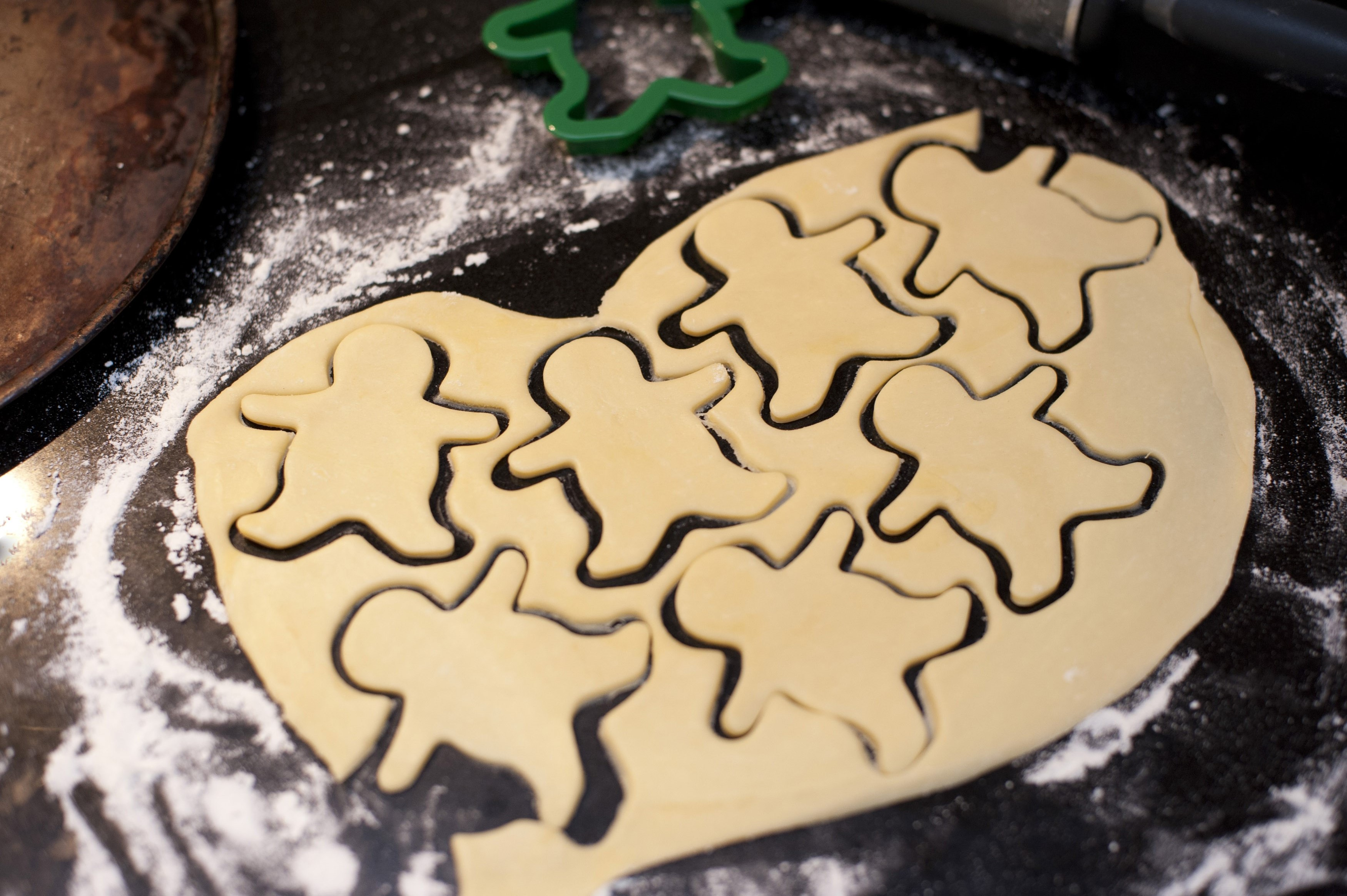 Rolled dough on a kitchen counter with cut out shapes of little figures while baking cookies or biscuits