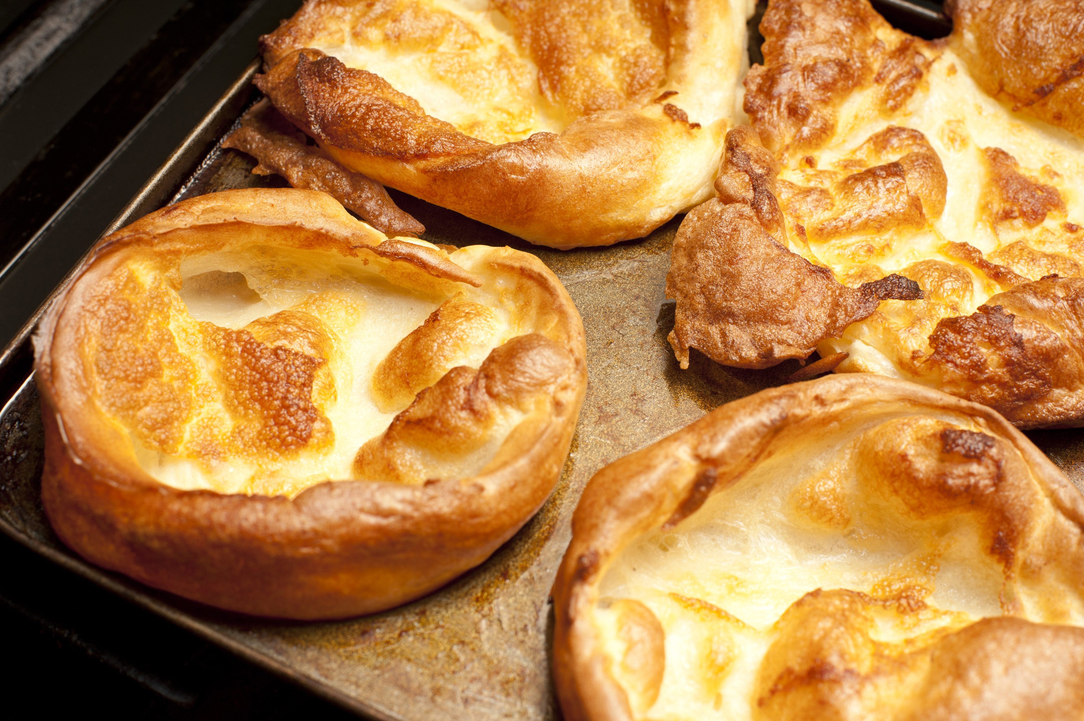 Large freshly baked golden Yorkshire puddings on a wooden board in the kitchen ready to be served for dinner, close up high angle view