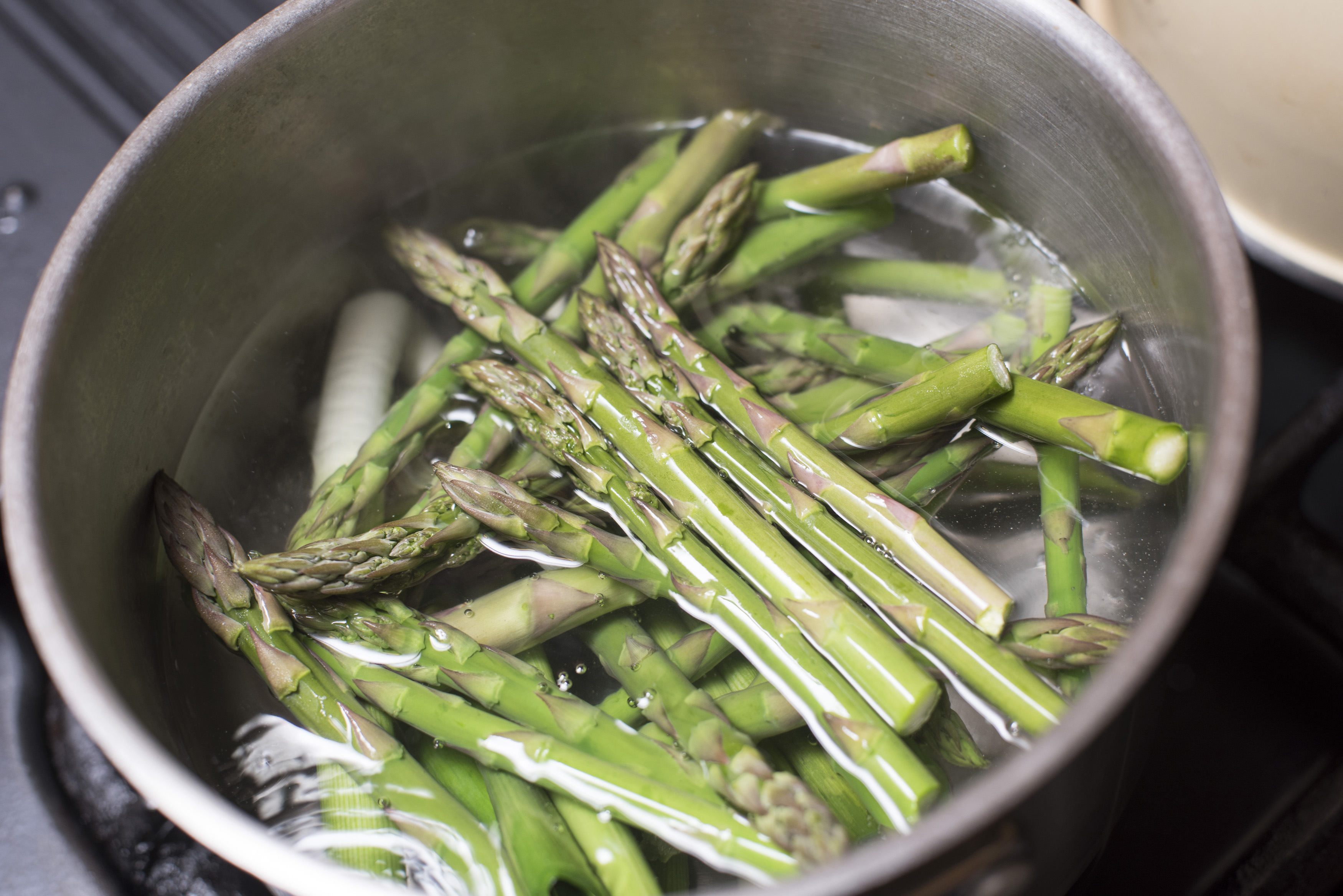 Fresh green asparagus spears boiling in a stainless steel saucepan on a gas hob