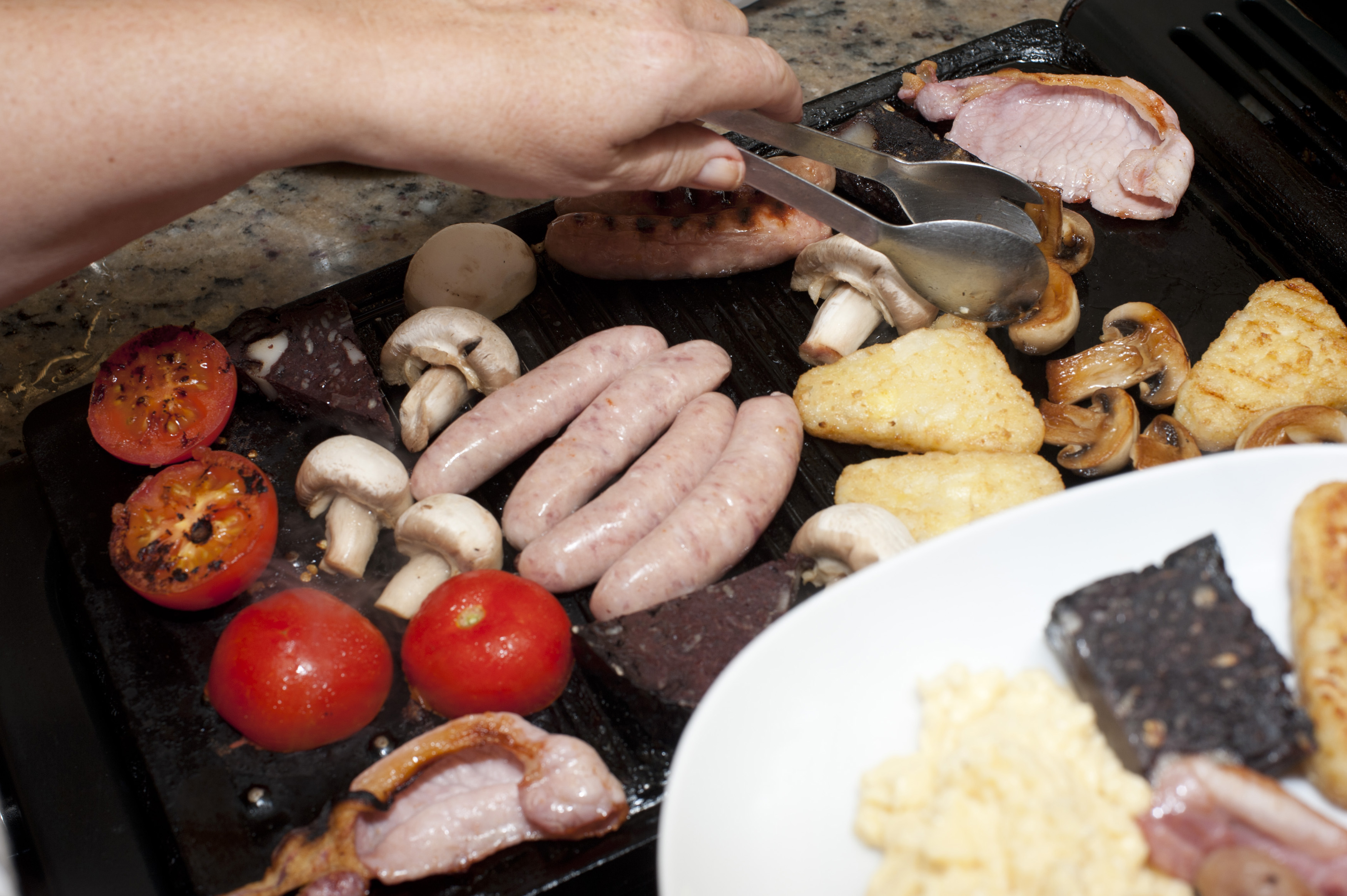Man preparing a wholesome breakfast serving bacon, black pudding, mushrooms sausages and tomato onto a plate from a hot griddle