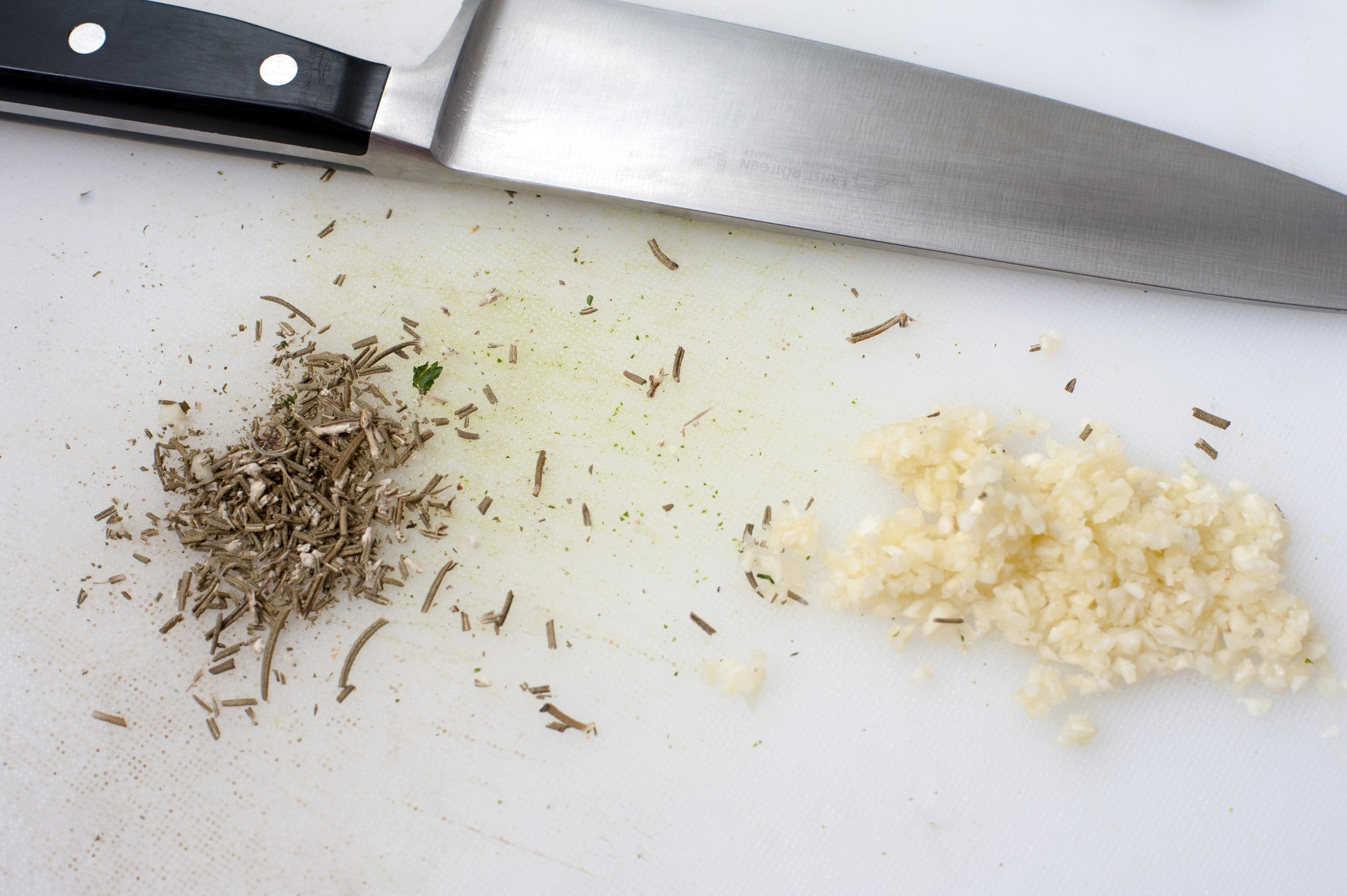 Finely chopped fresh garlic and herbs on a kitchen chopping board with a chefs knife for use in a cooking recipe as a seaoning and aromatic flavouring