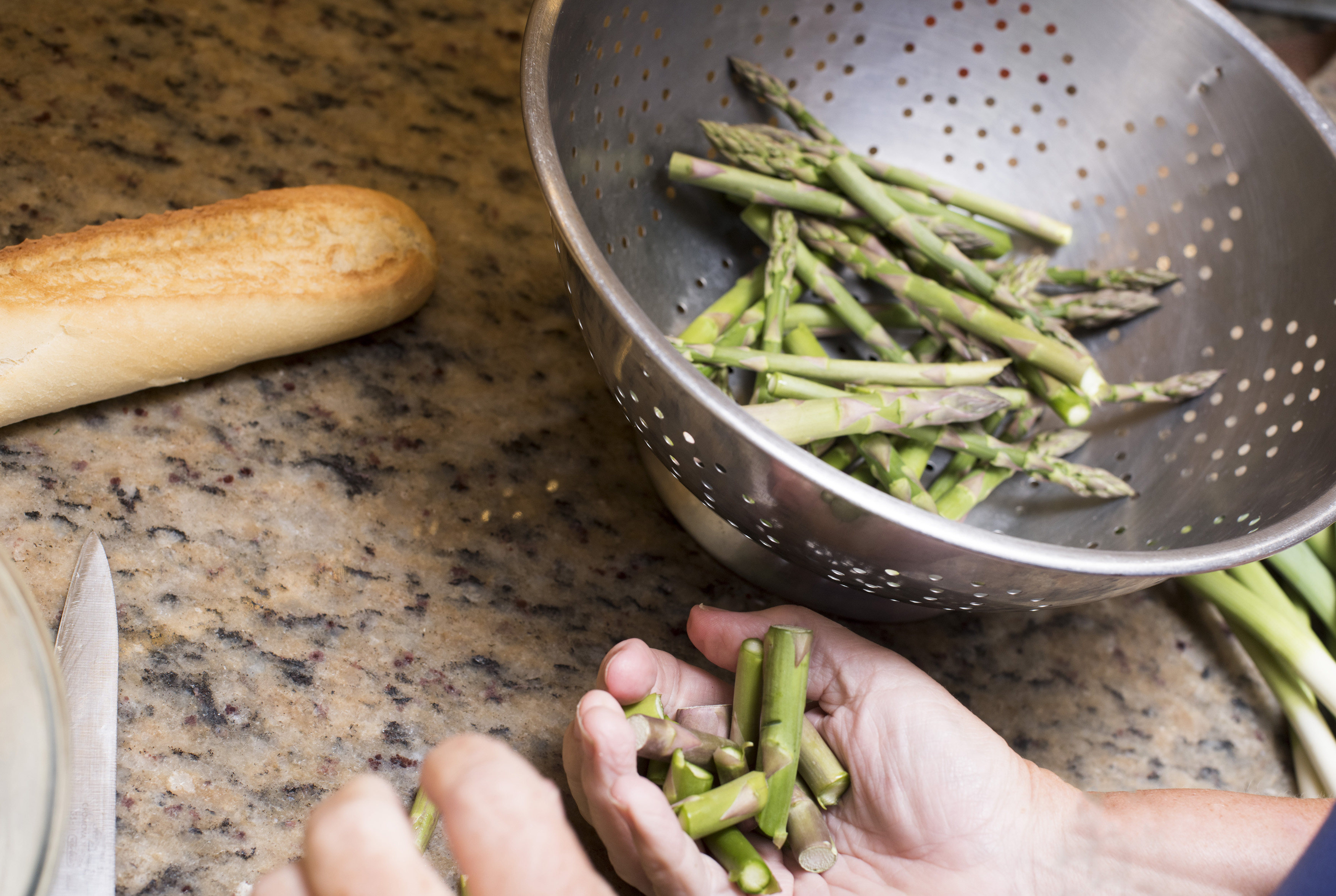 Chef dicing fresh green asparagus tips or spears that have been washed in a colander for inclusion in a recipe