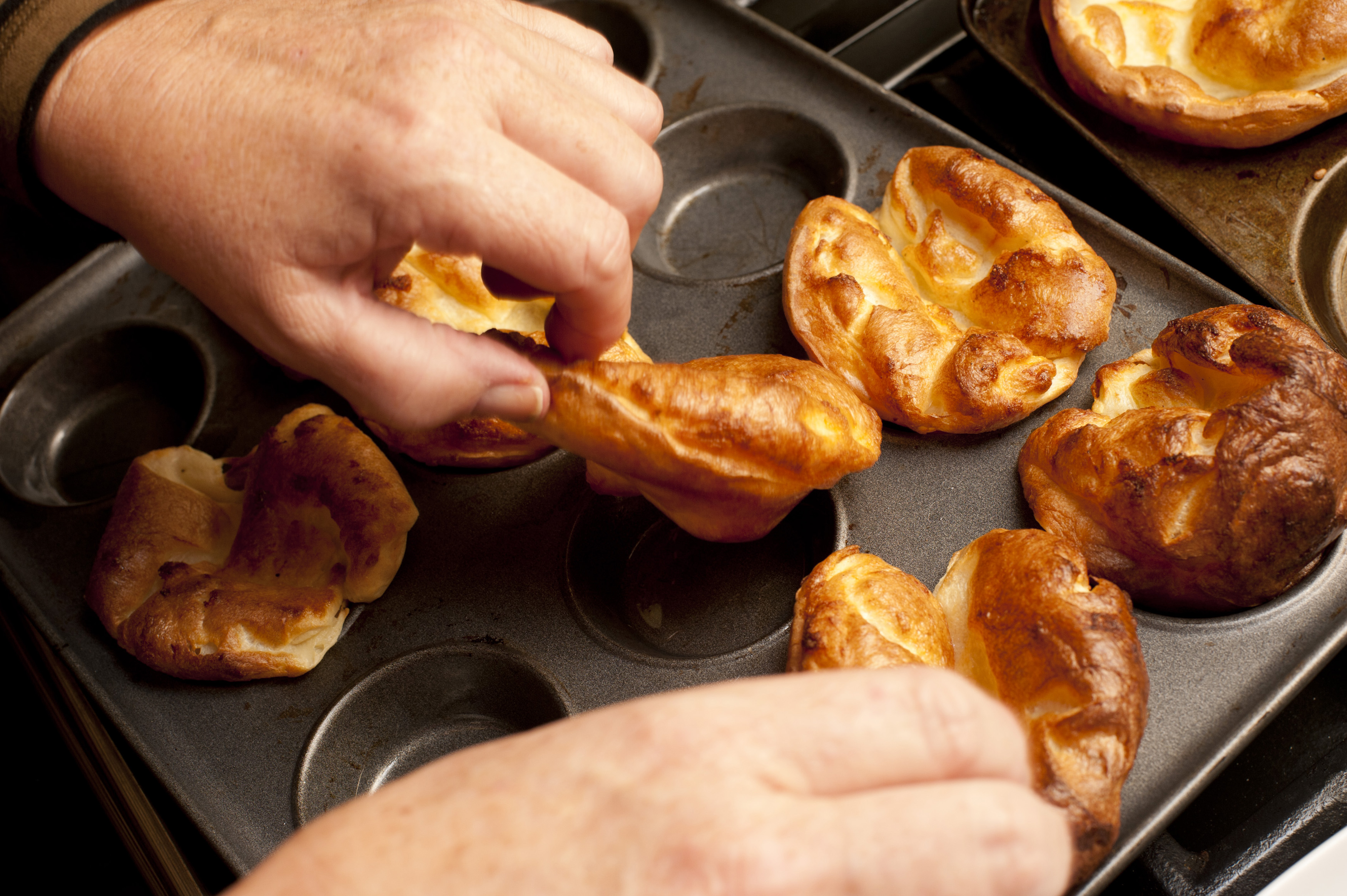 Close up on the hands of a male chef removing cooked individual golden Yorkshire puddings from a baking tray fresh from the oven