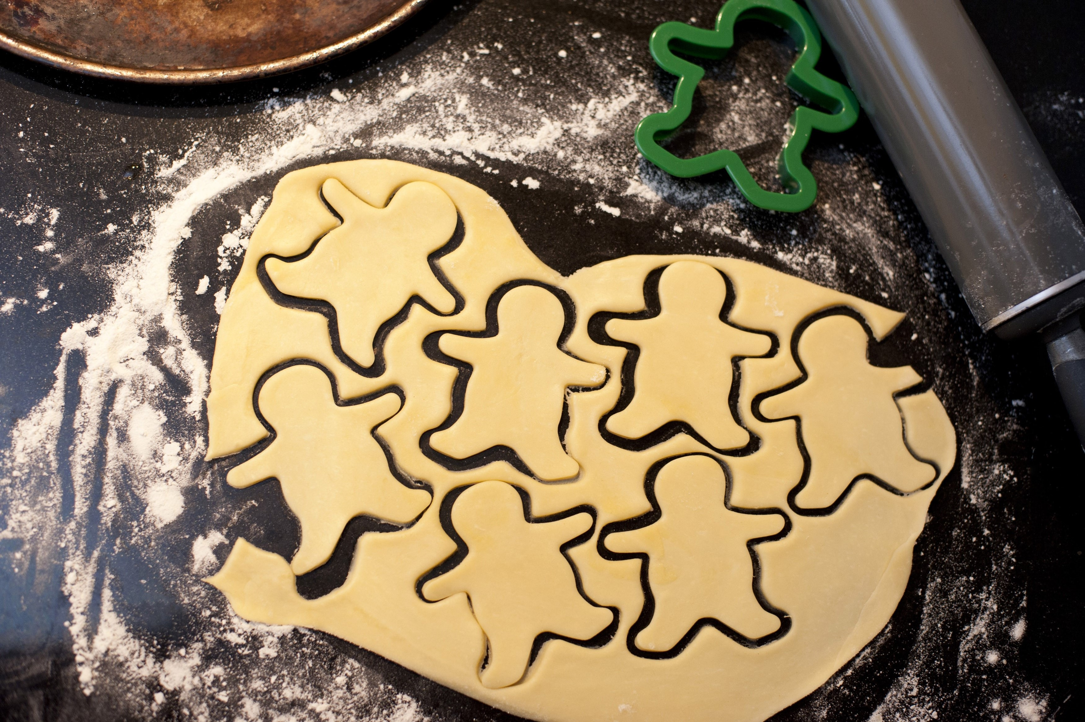 Overhead view of rolled pastry dough with cut out shapes of little figures while cutting cookies for a kids party celebration