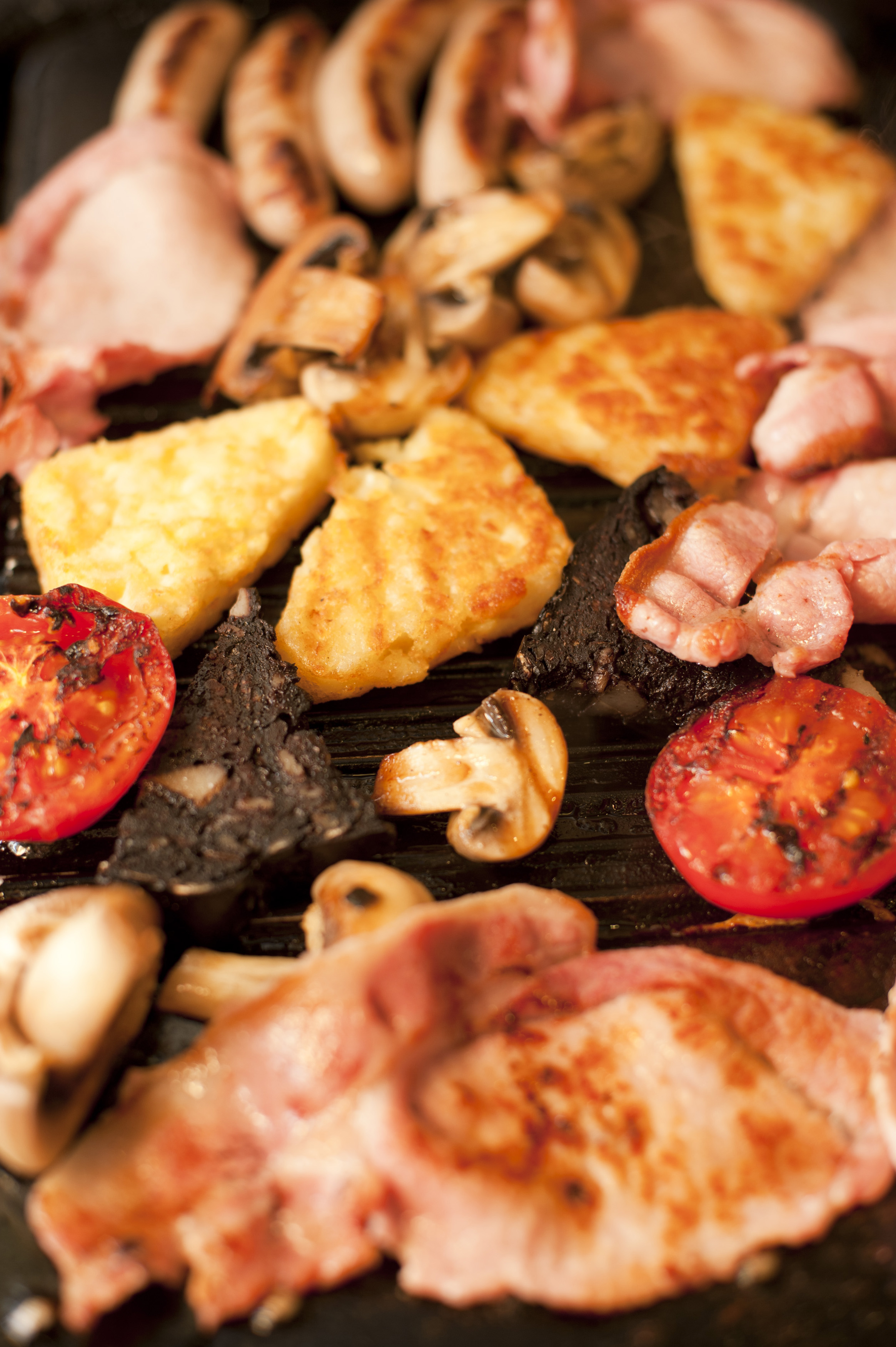 Close up view of grilled tomato and mushroom cooking besides four sausage links and other meats