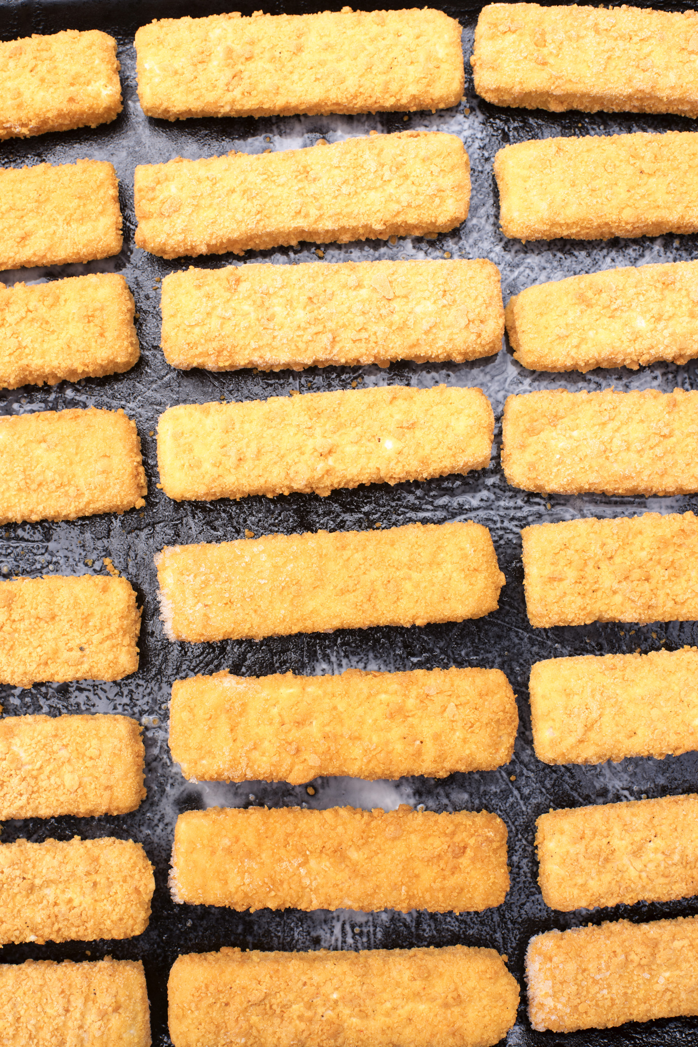 Frozen fish fingers laid out in neat rows to defrost for oven baking, viewed from above in a catering concept