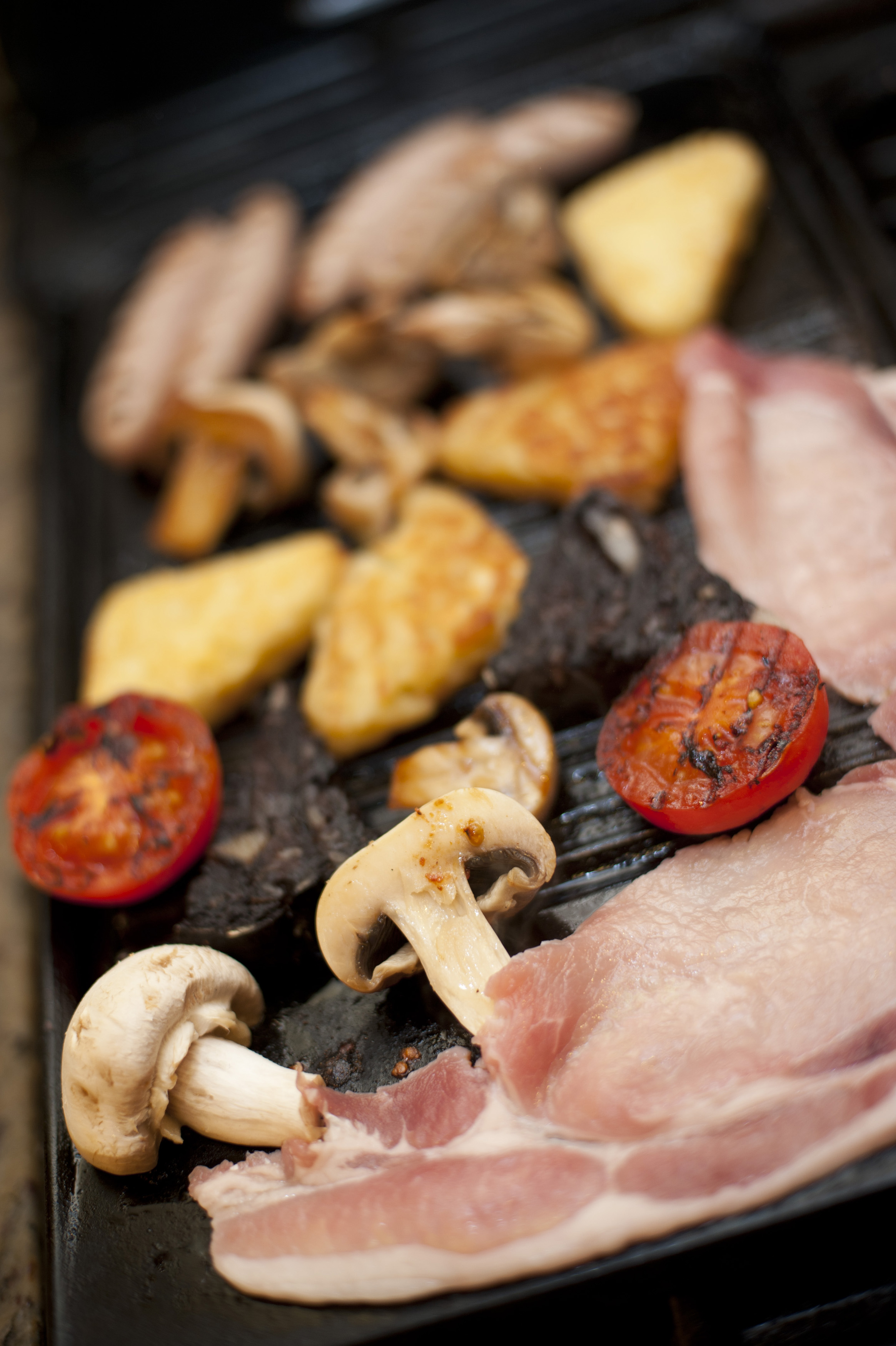 Full cooked English breakfast with bacon rashers, mushrooms, tomato French toast and sausages on a griddle with shallow dof