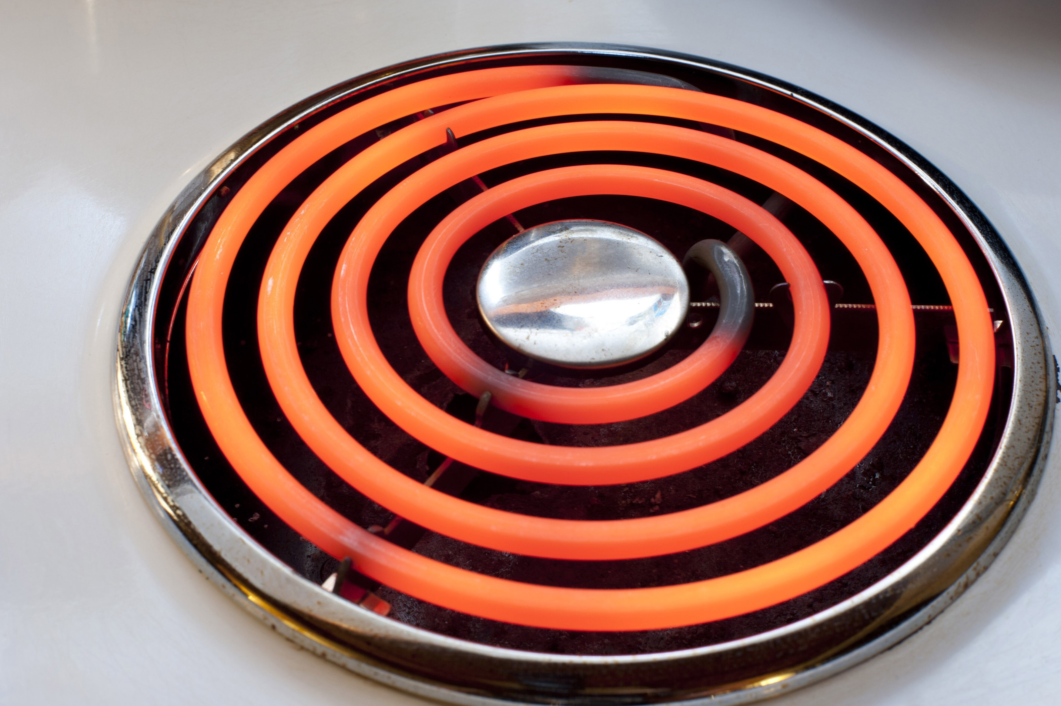 Red hot spiral electric hotplate on a stove top in a domestic kitchen for cooking food