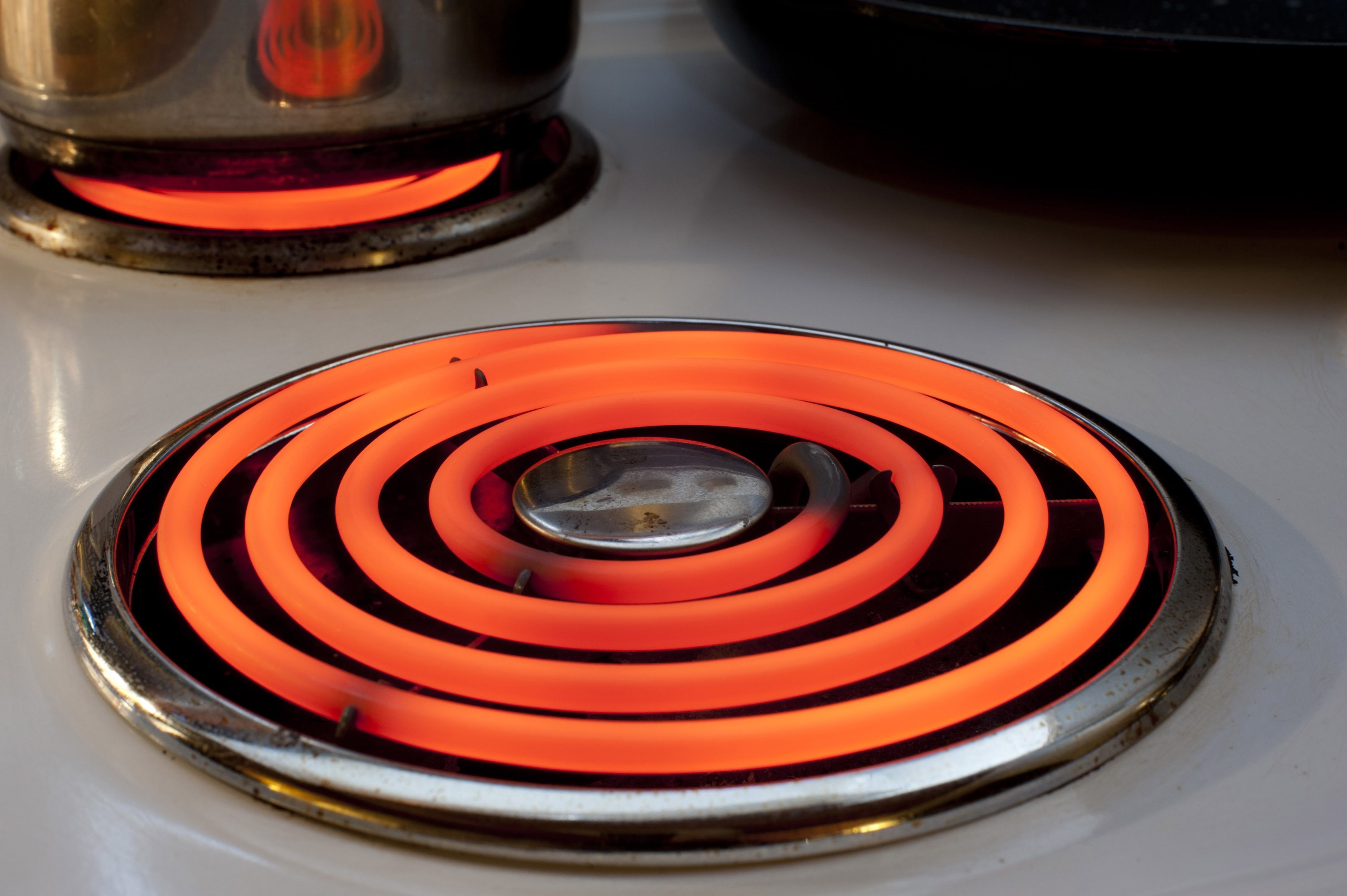 Red hot spiral ring element on an electric stove in the kitchen providing power and energy for cooking the food