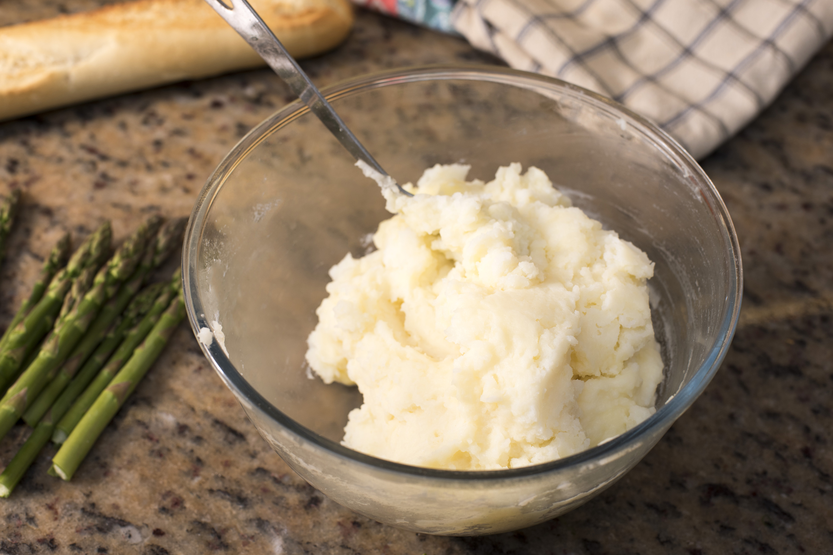 Bowl of freshly mashed cooked potato standing alongside fresh asparagus tips on a marble kitchen counter