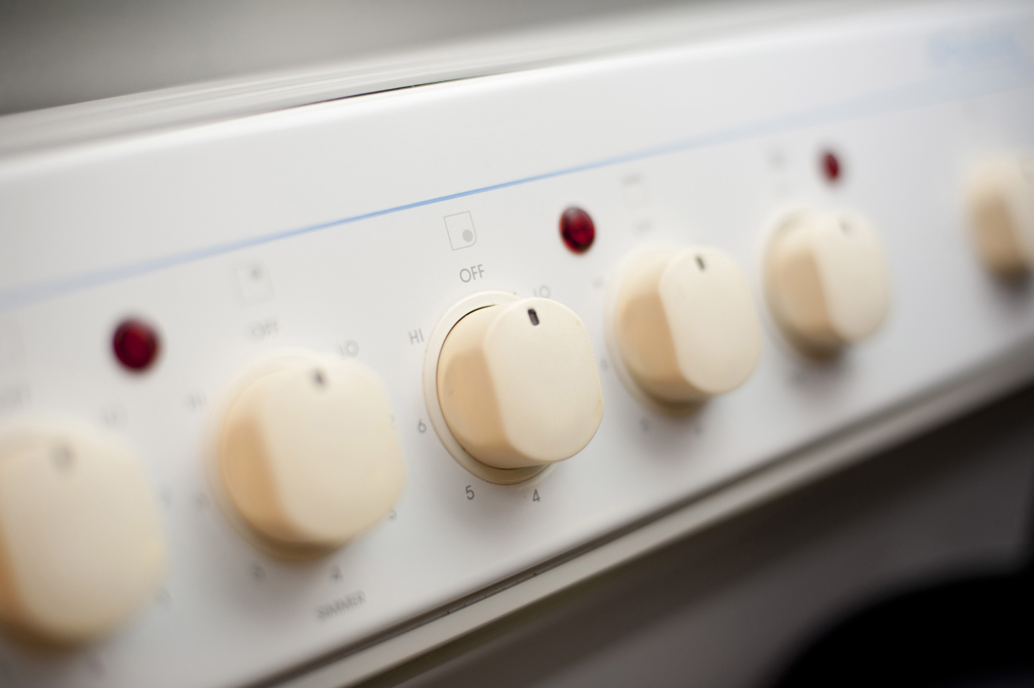 Receding oblique row of control dials and thermostats on a domestic oven with shallow dof