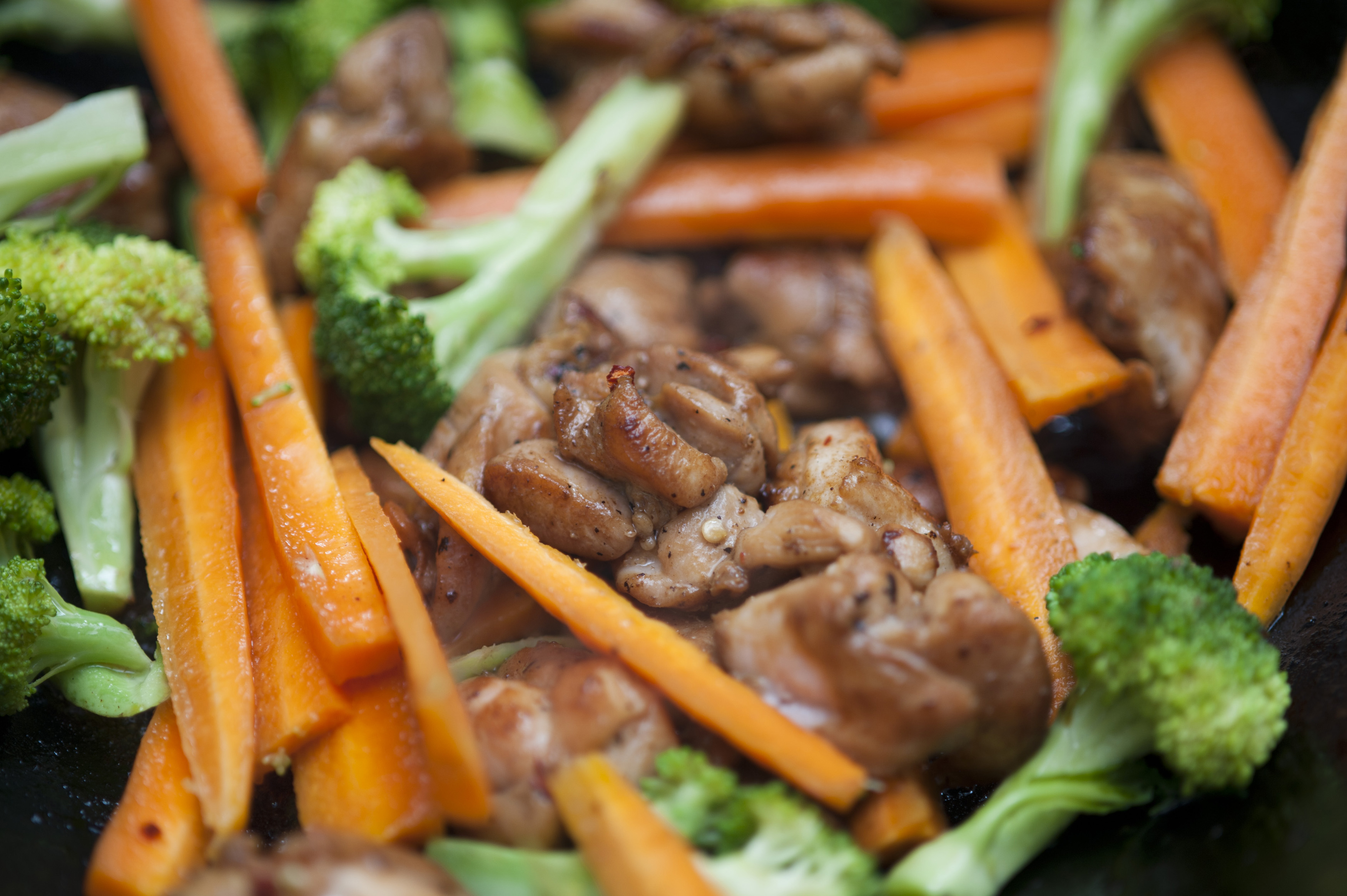 Close up view of delicious cooked vegetables such as carrot sticks and chopped broccoli with small cuts of meat