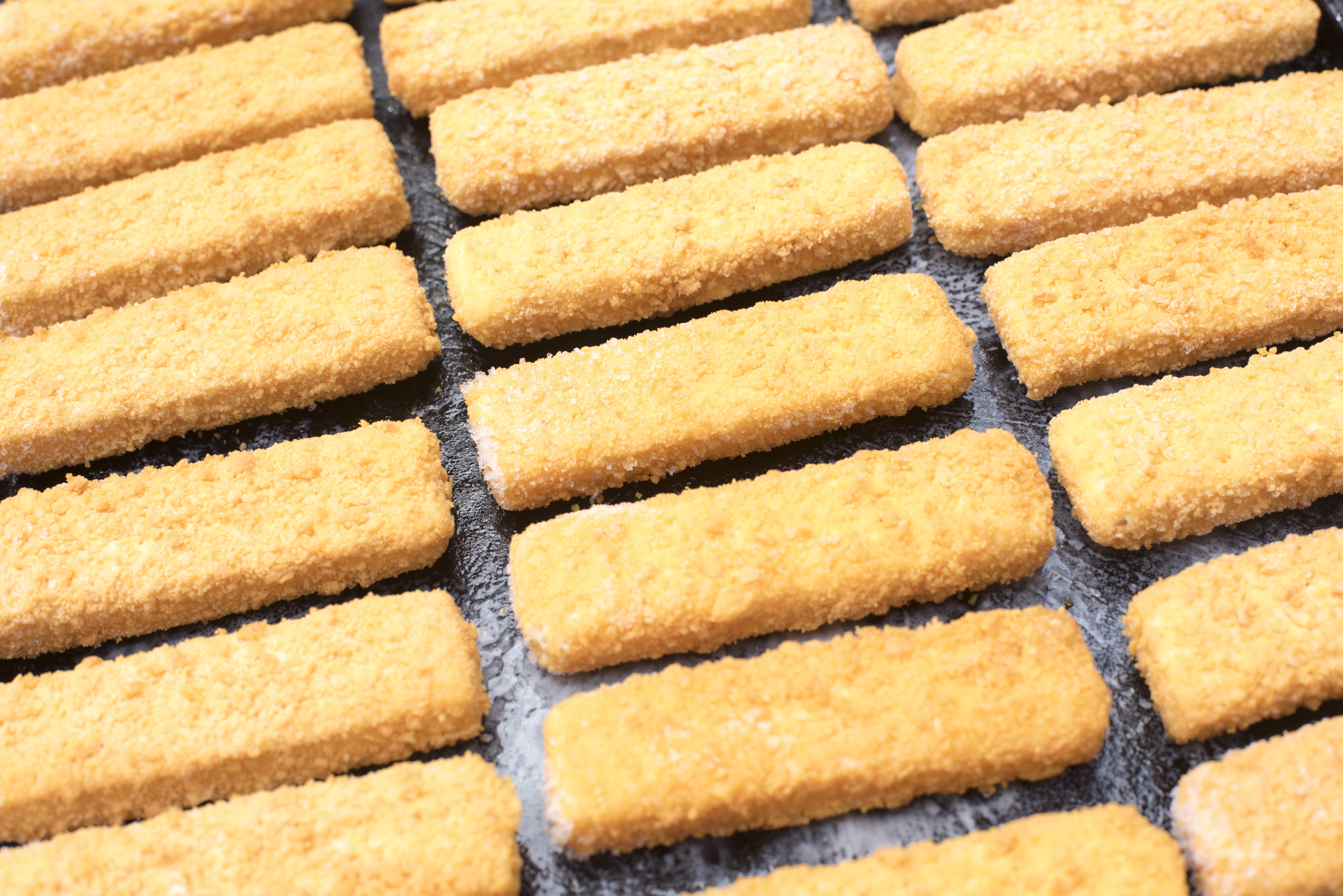 Full frame top down view on ready to bake breaded fried fish finger snacks on black pan