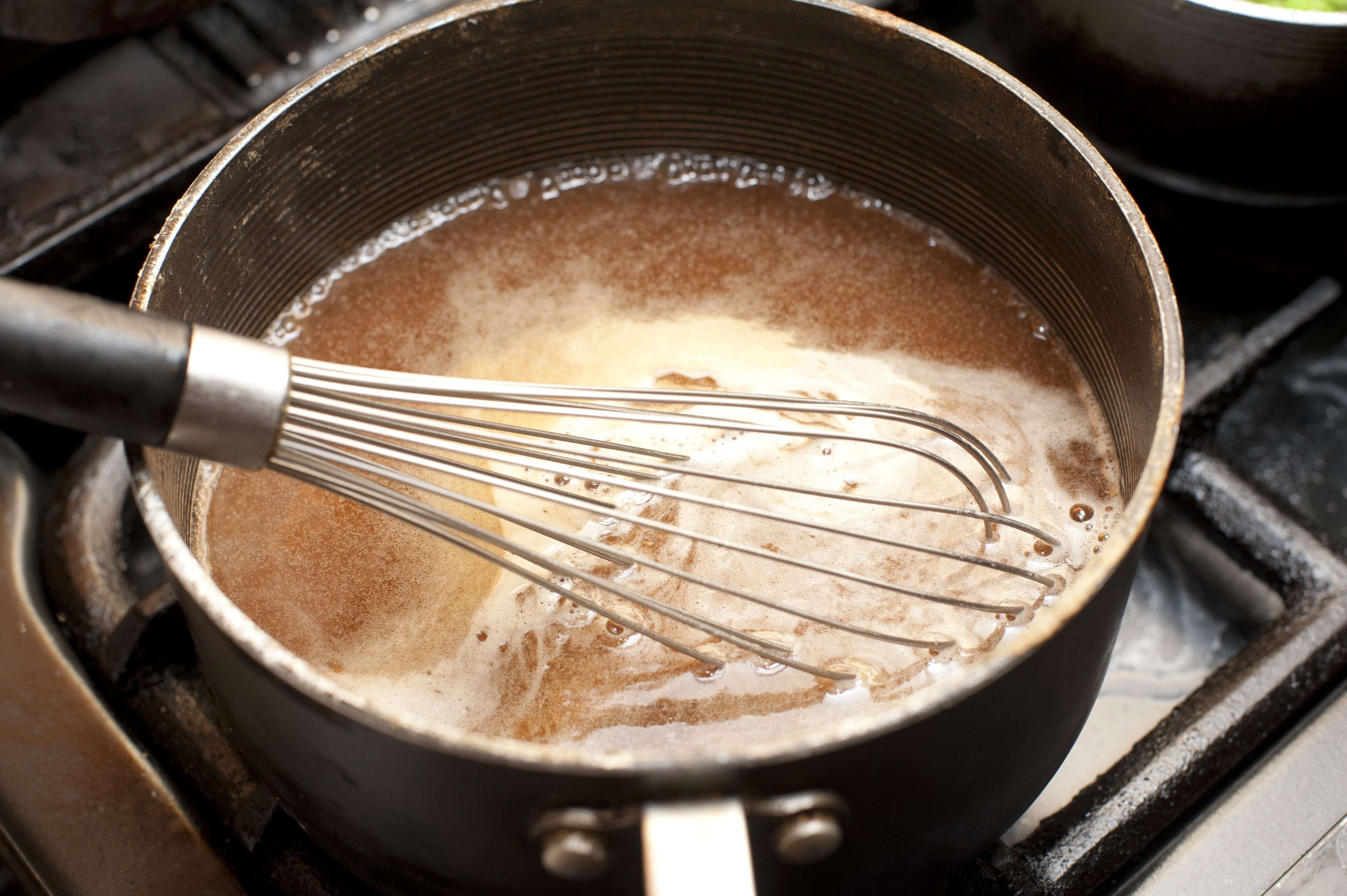 Close up view of brown gravy simmering in sauce pan atop gas range as wire whisk rests inside it