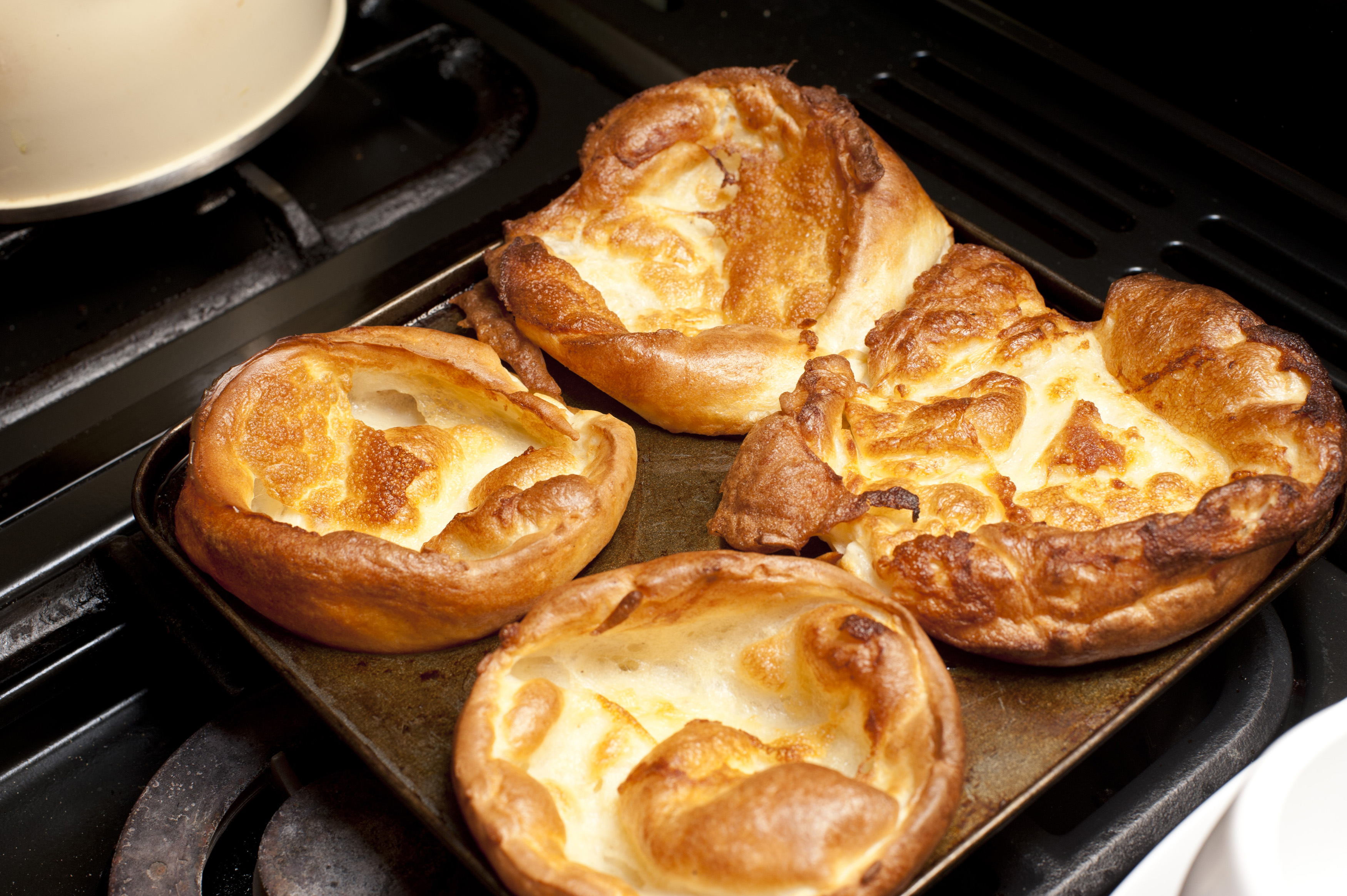 Close up on four freshly baked round Yorkshire pudding buds on square tray on top of slove