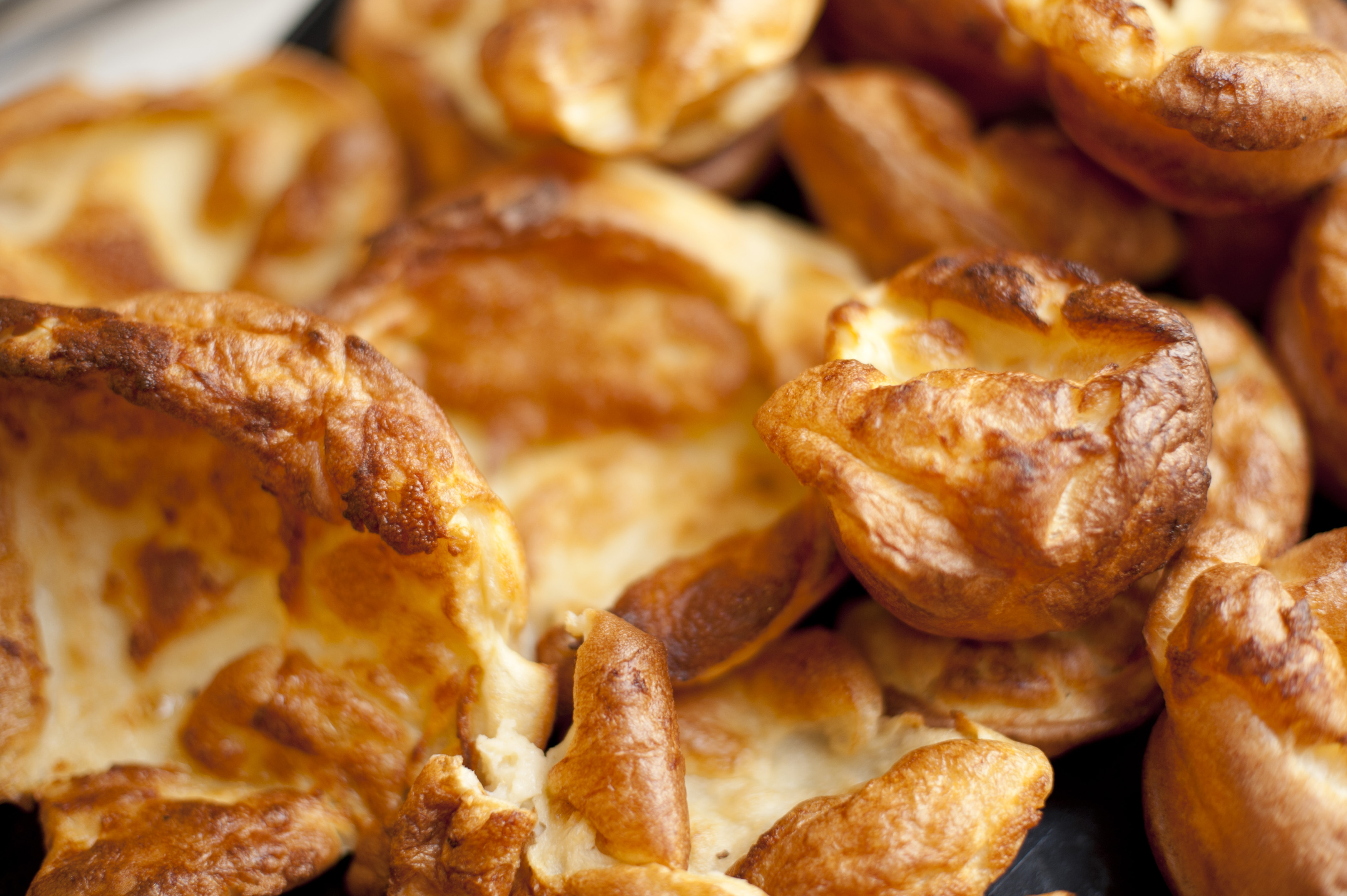Multiple small individual Yorkshire puddings in a full frame food background conceptual of catering or a restaurant