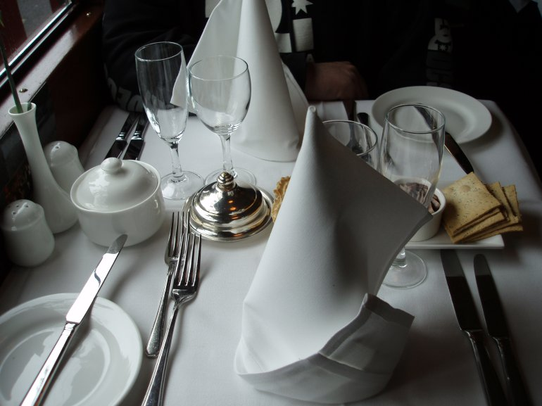Formal place settings with white linen crockery silverware and glassware at an intimate table & Formal place settings at a table for two - Free Stock Image